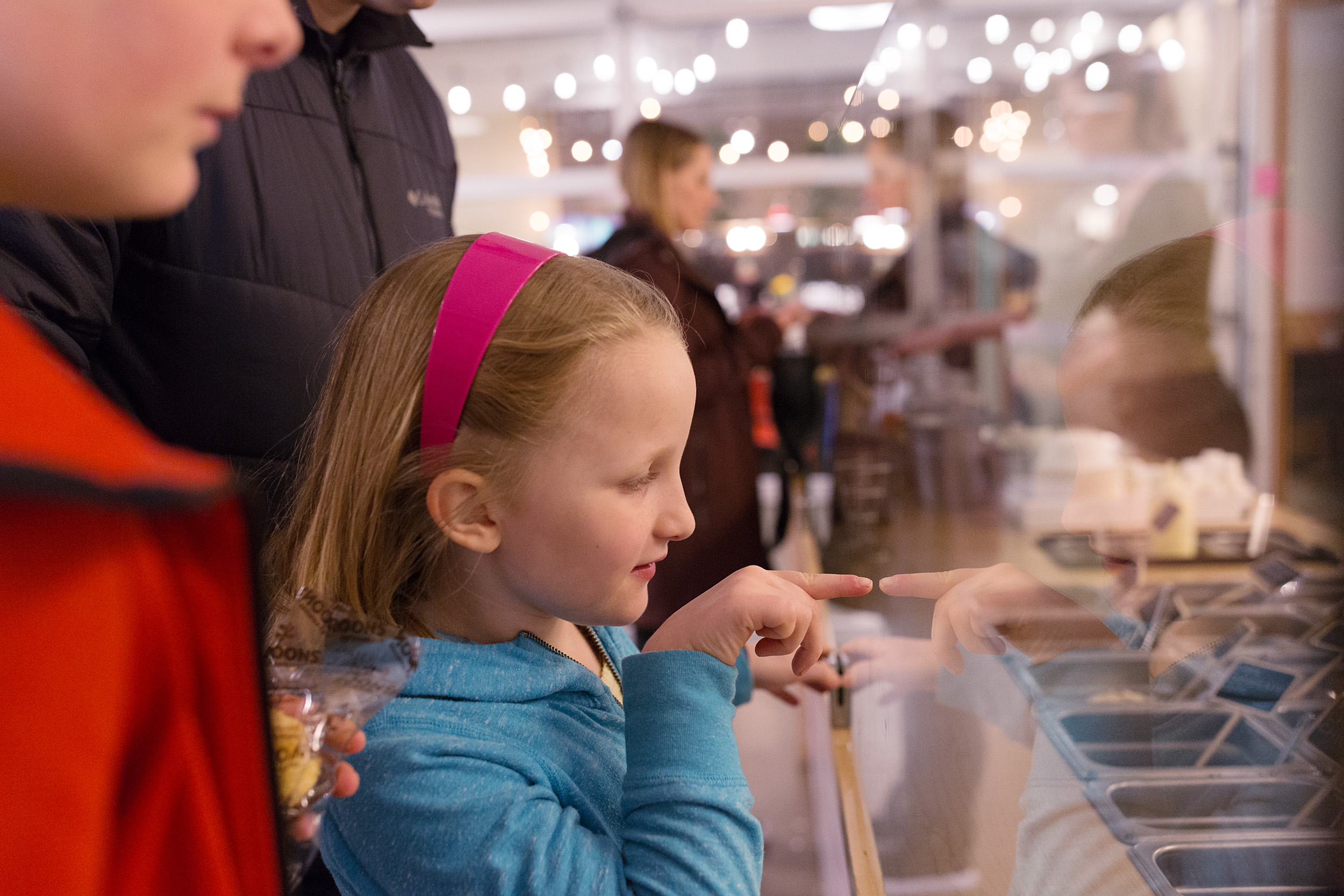 girl points at the toppings case choosing her favorites