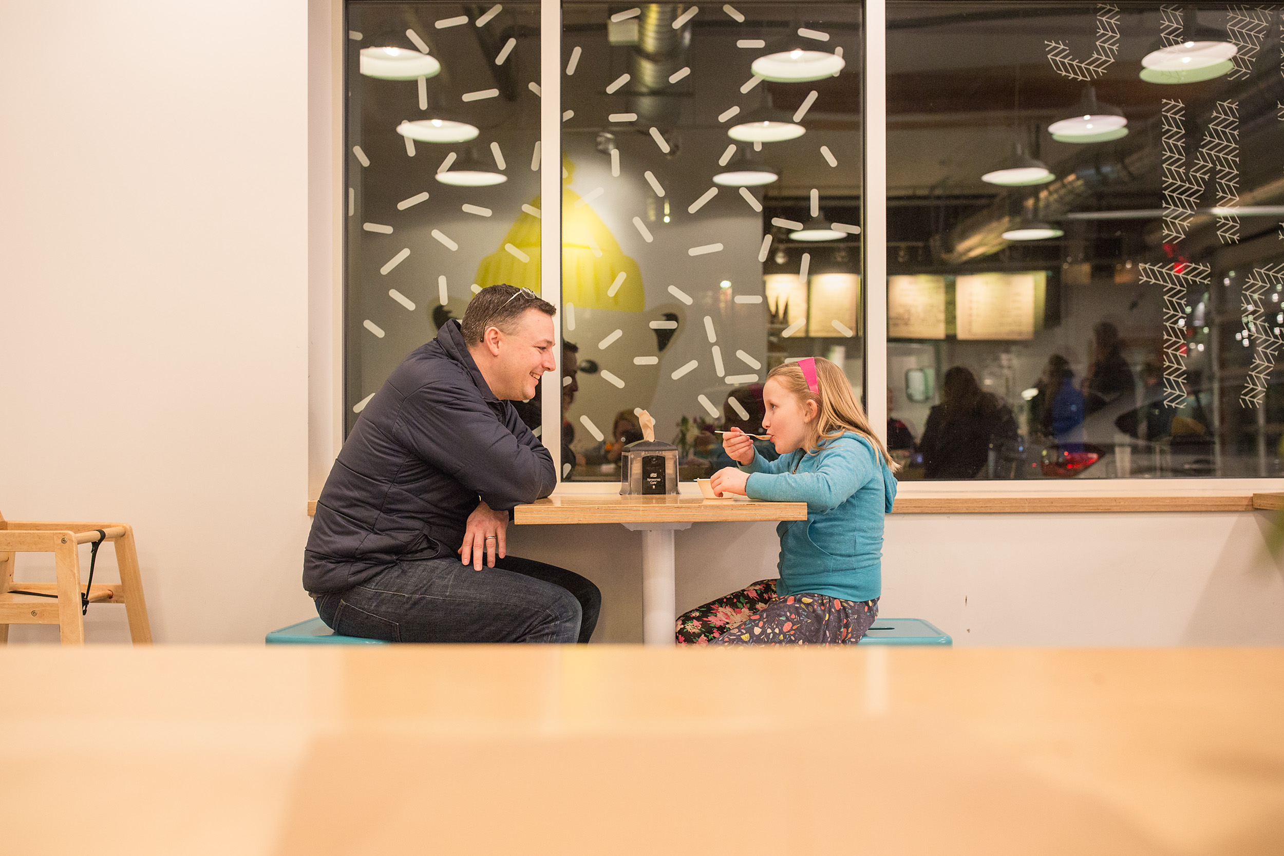 dad and daughter laughing and eating fro yo