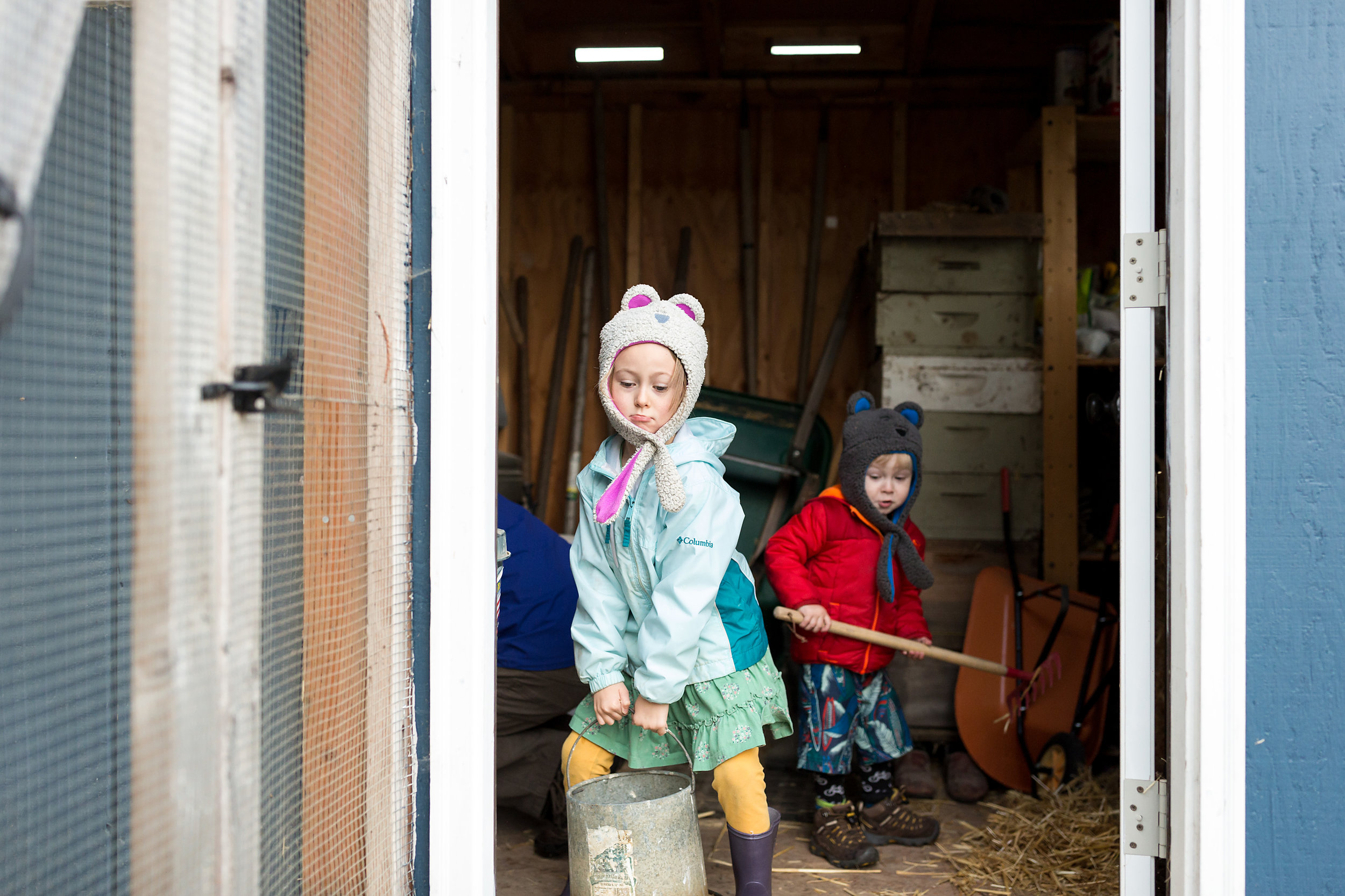 Girl hefts bucket from shed while brother rakes straw and looks on