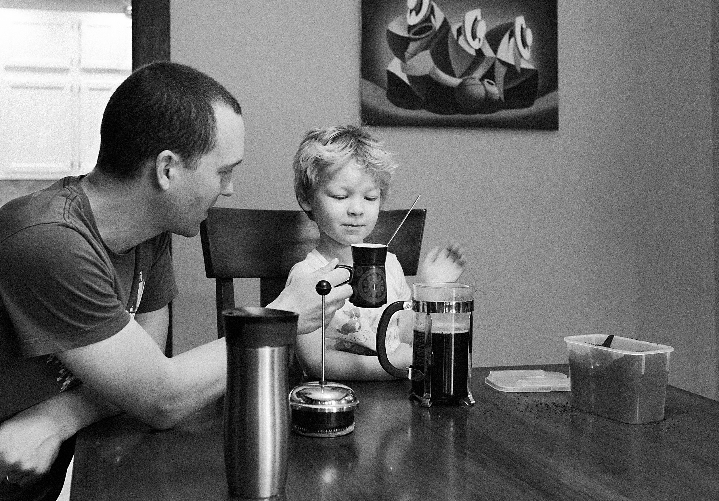 father and son make coffee together