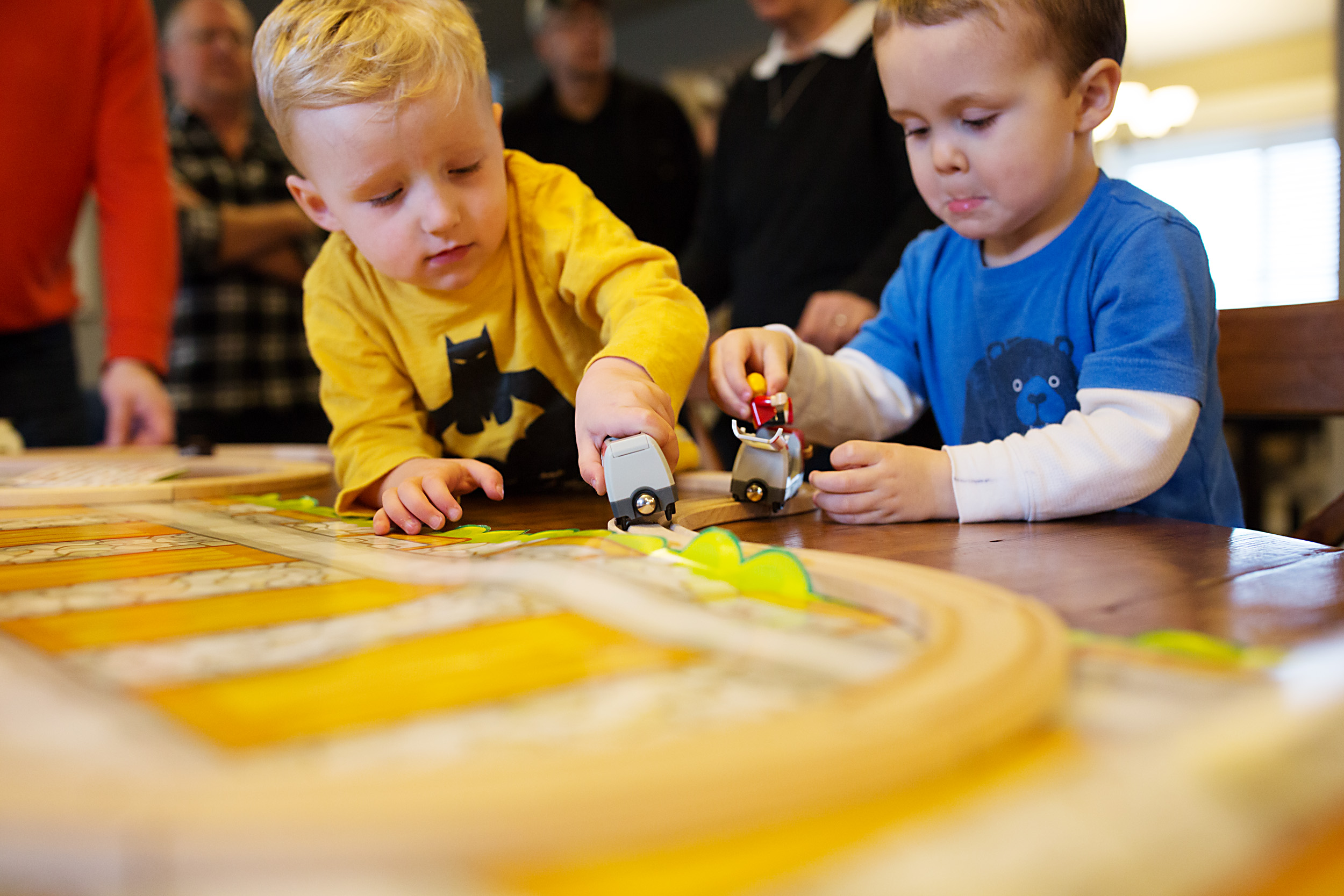 two boys play with trains on dining room table