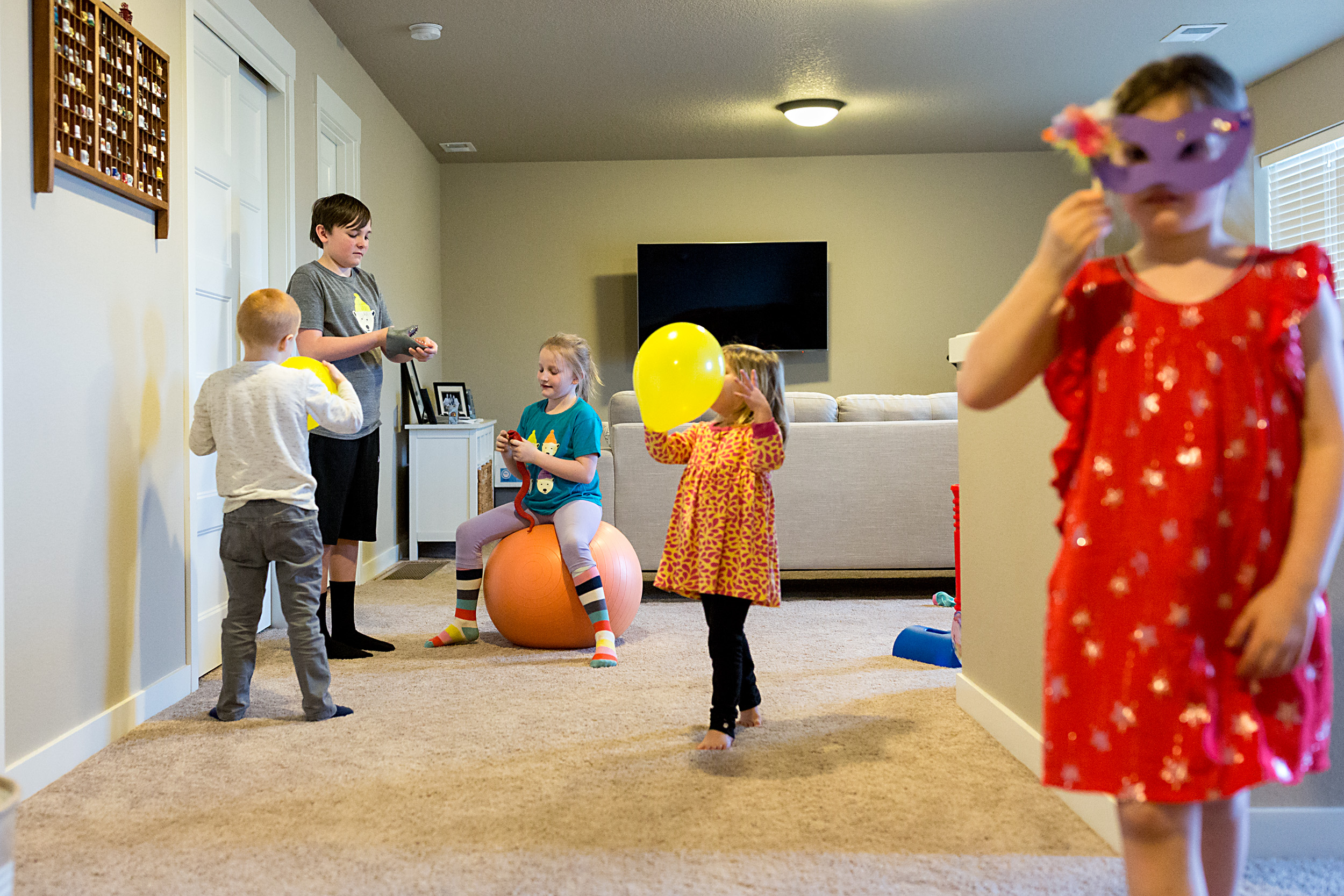 a handful of kids playing upstairs with balloons, masks and balls