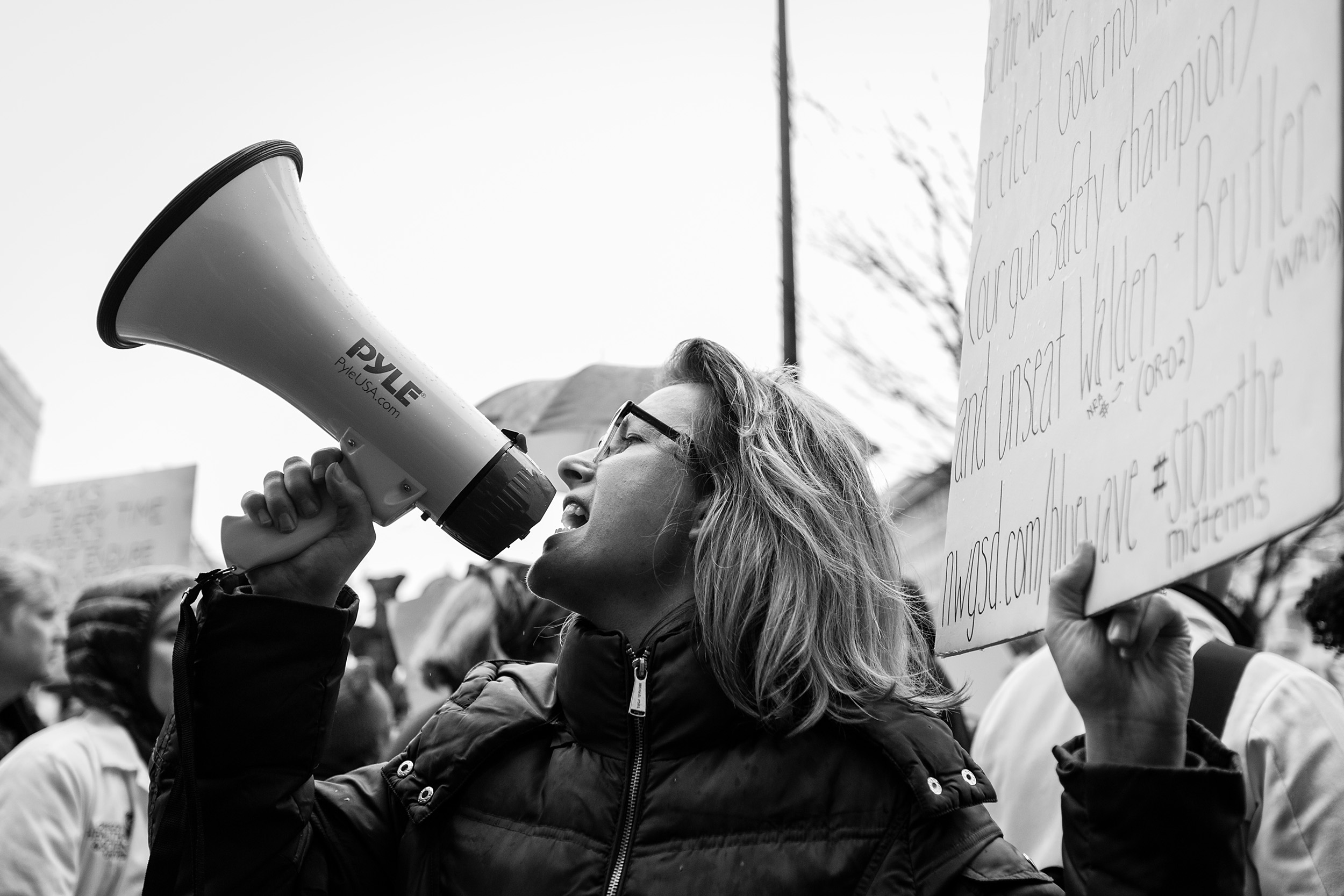 woman with loudspeaker leads crowd in chant