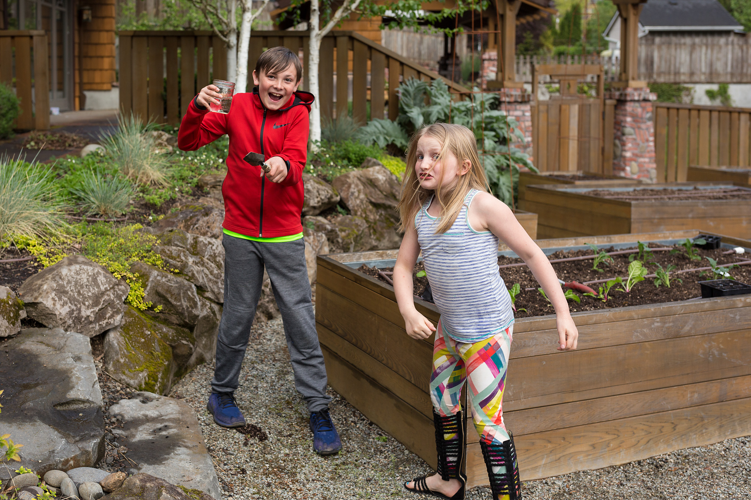 boy laughing and sister angry after their water fight