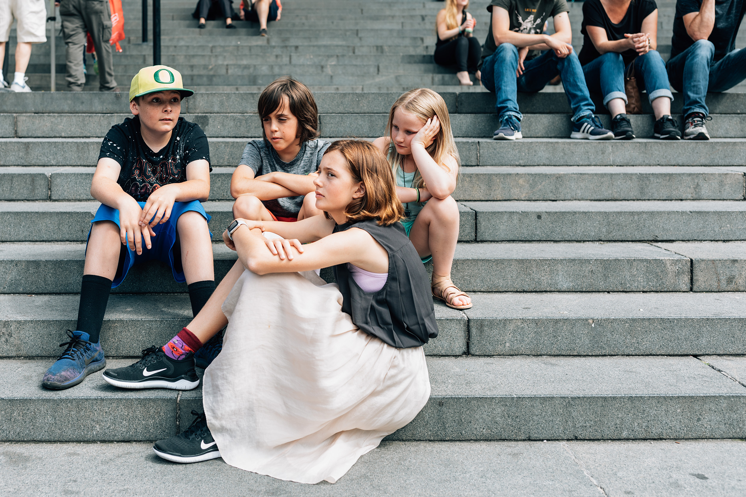 Four bored children waiting on the stone stairs to enter a church in London