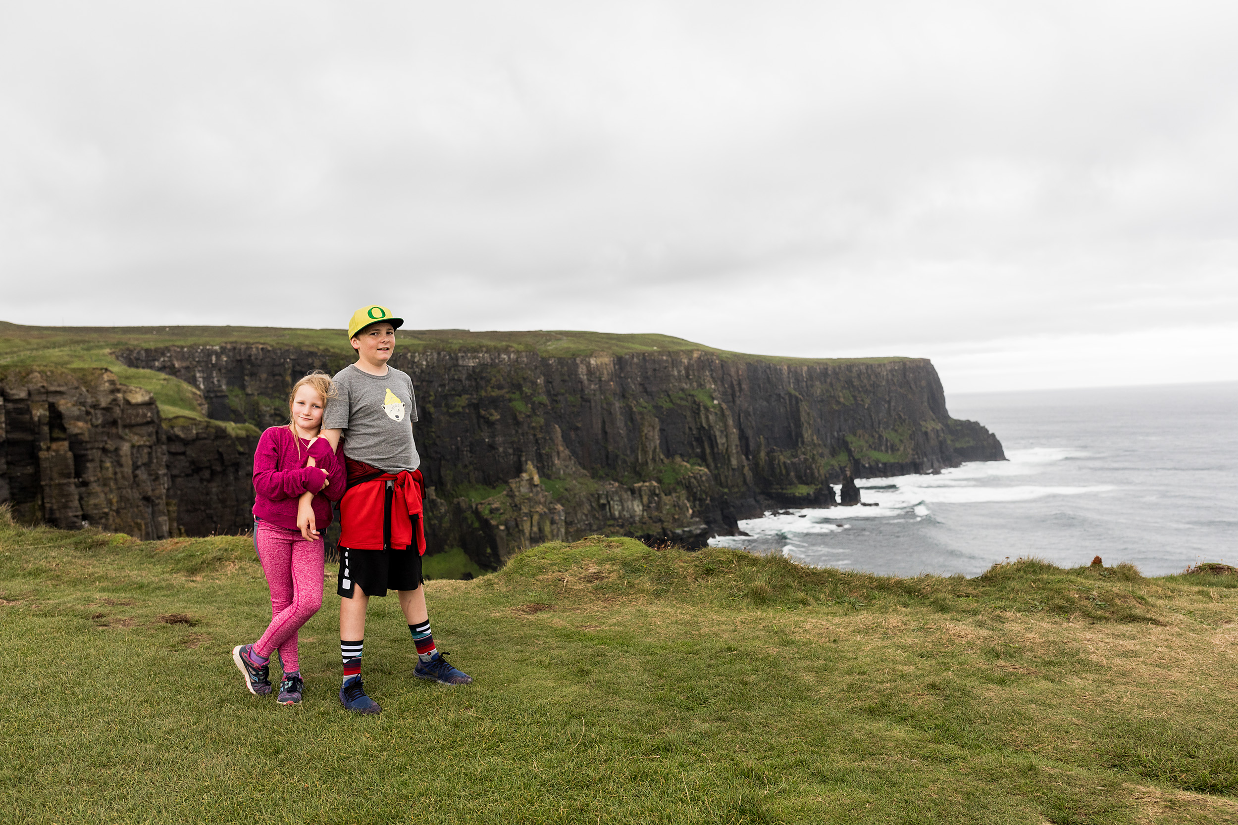 Sister and brother stand on the Cliffs of Moher in Ireland