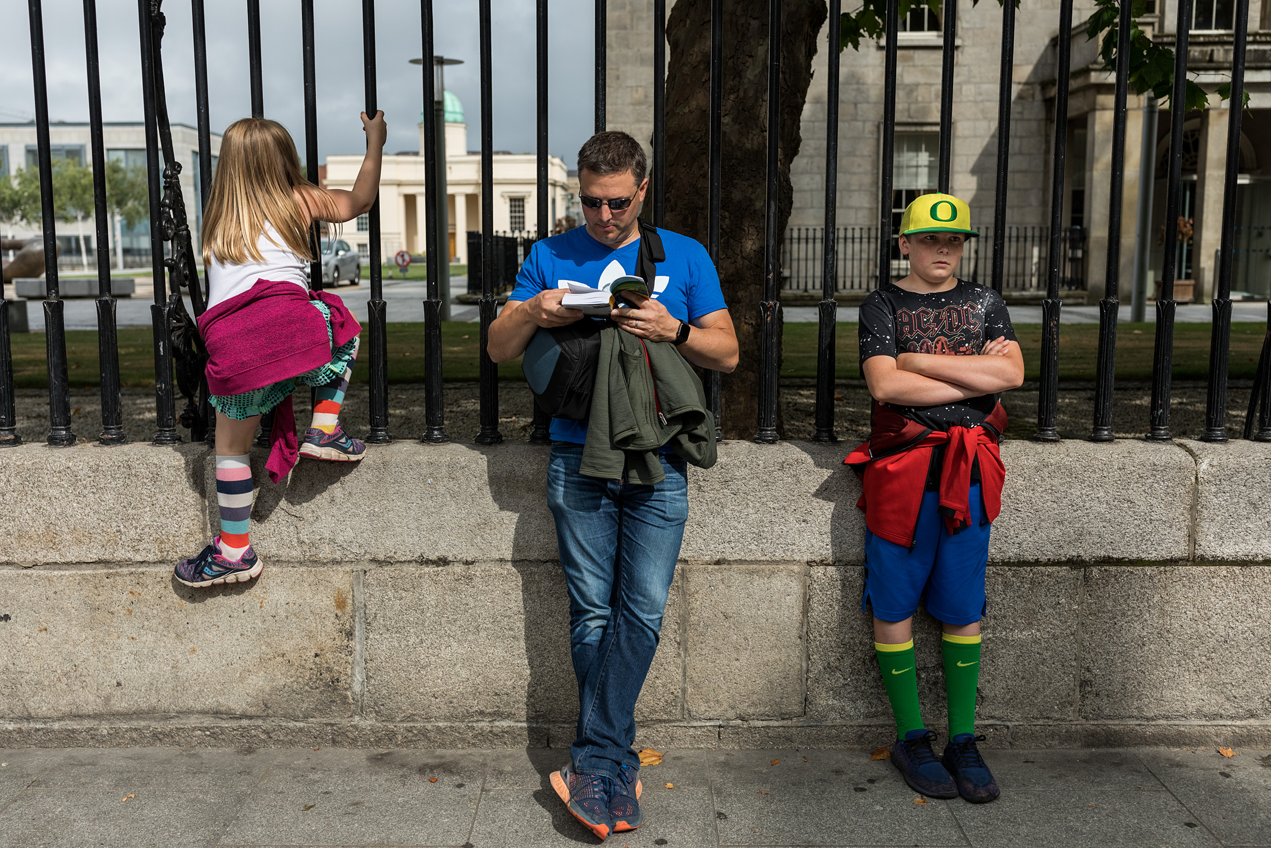 A dad looks through a tour book while his kids are bored out of their minds in Dublin, Ireland