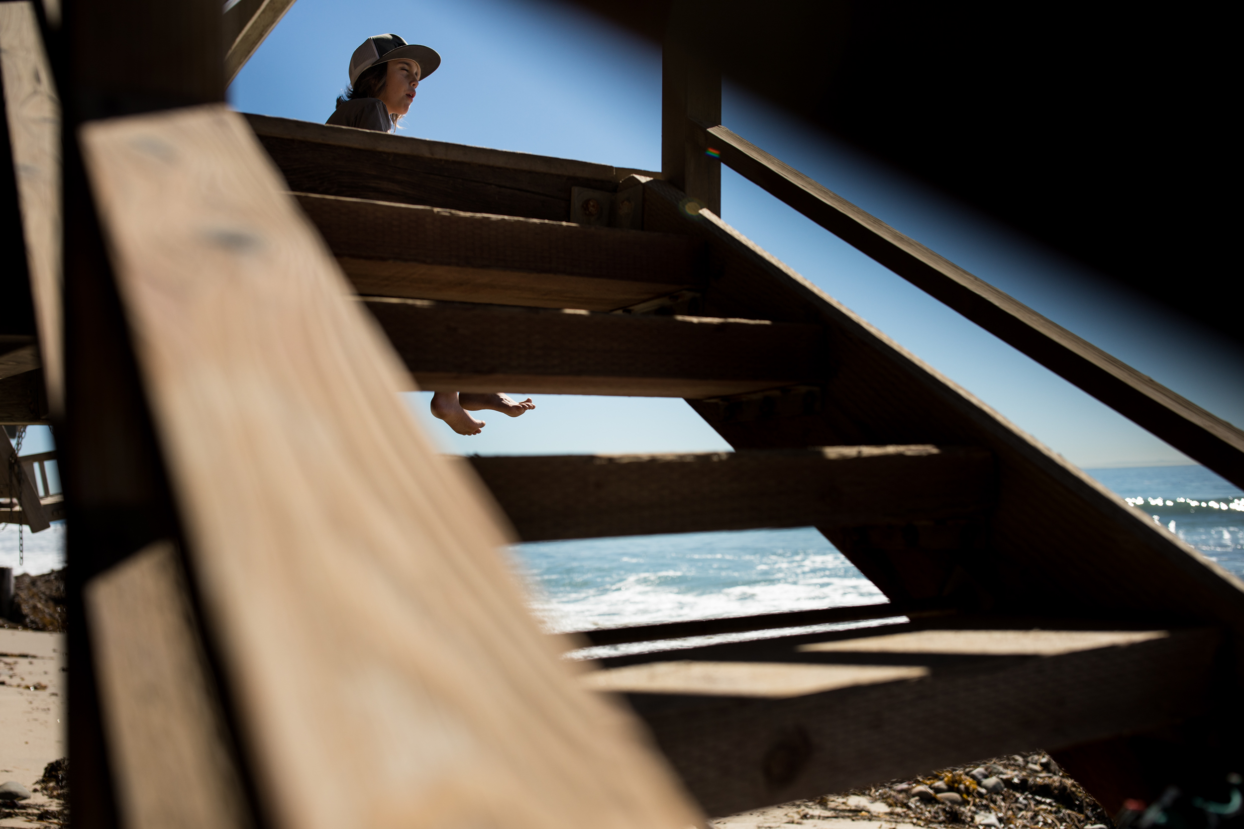 A boy sits on the deck dangling his feet over the beach below