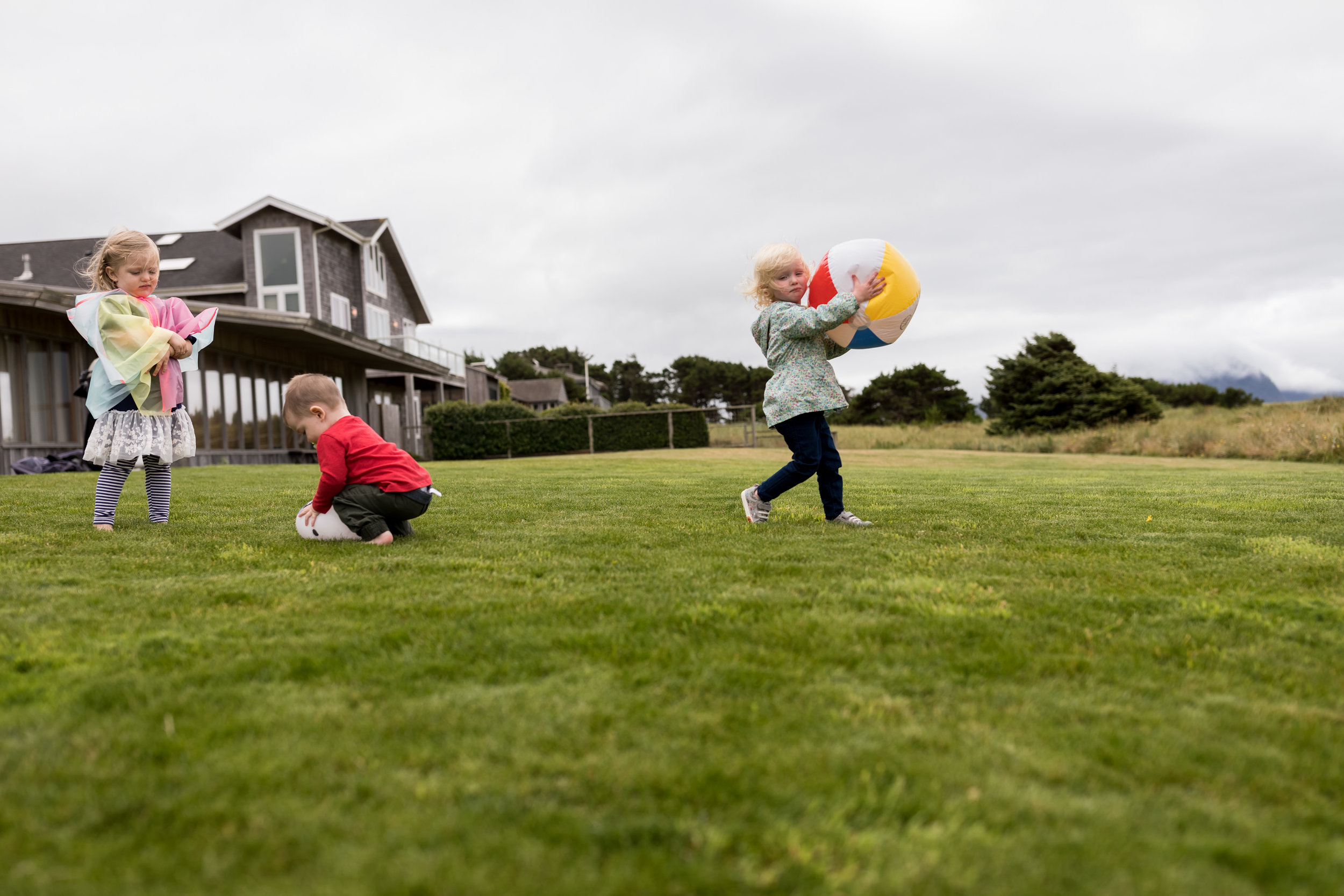 Girls steals ball from cousin while younger brother squishes a balloon.