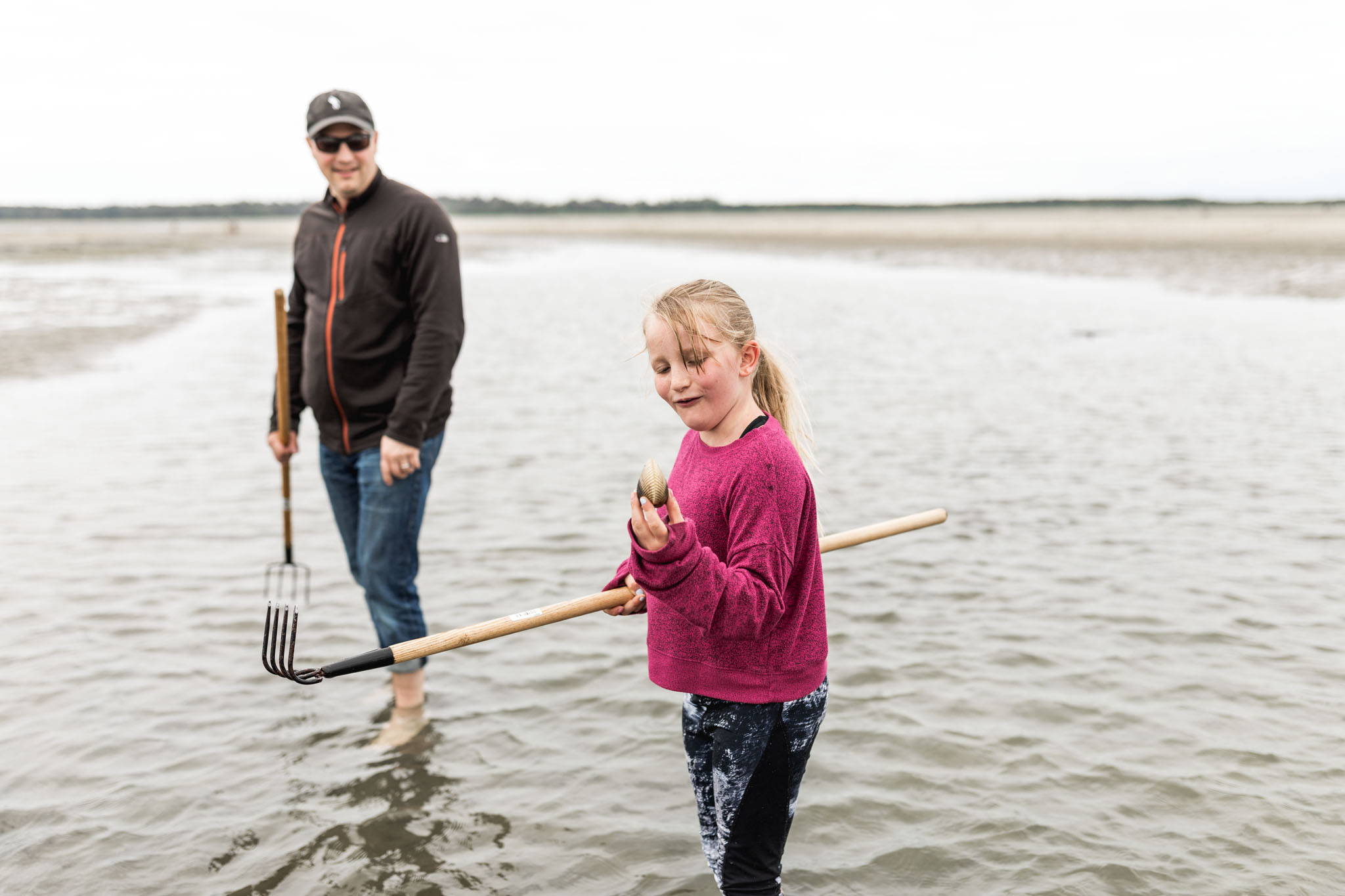 Girl is surprised by the size of the clam she has raked from the sand