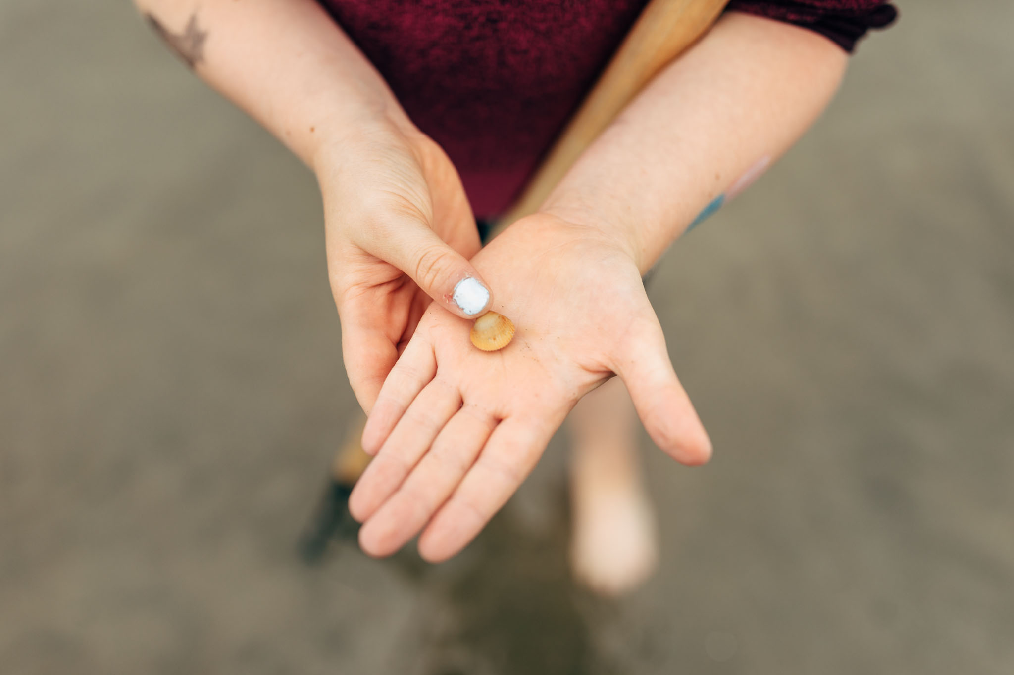 Girl holds tiny clam in palm of hand