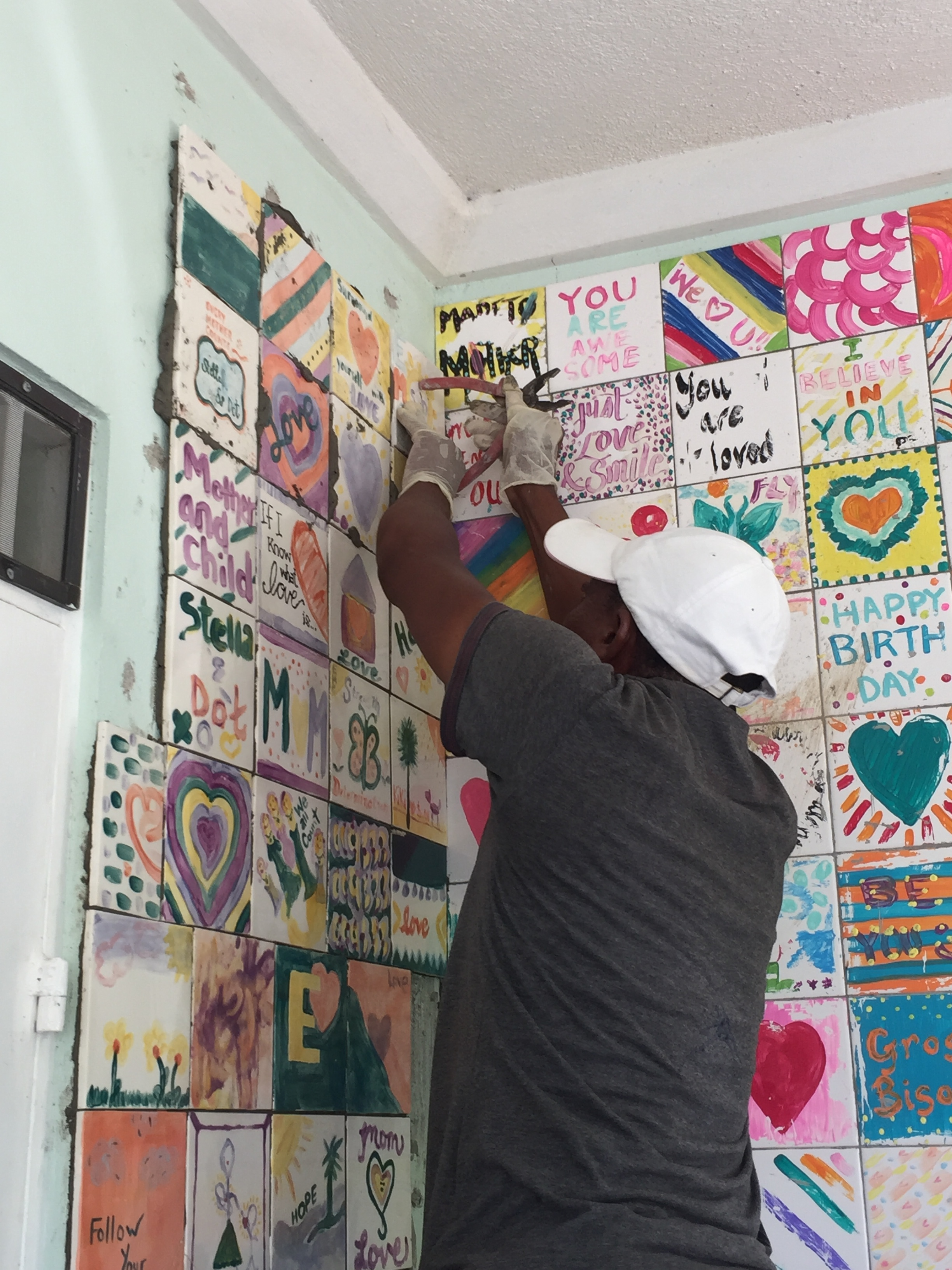 Installing the last few tiles decorated by Stella & Dot Stylists at the Carrie Wortham Birth Center