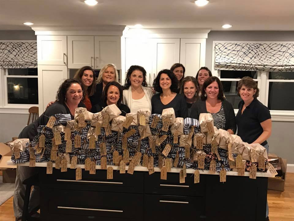 Stylist Debbie Brosnan and her team with 90 Chemo Care Poufs ready to donate