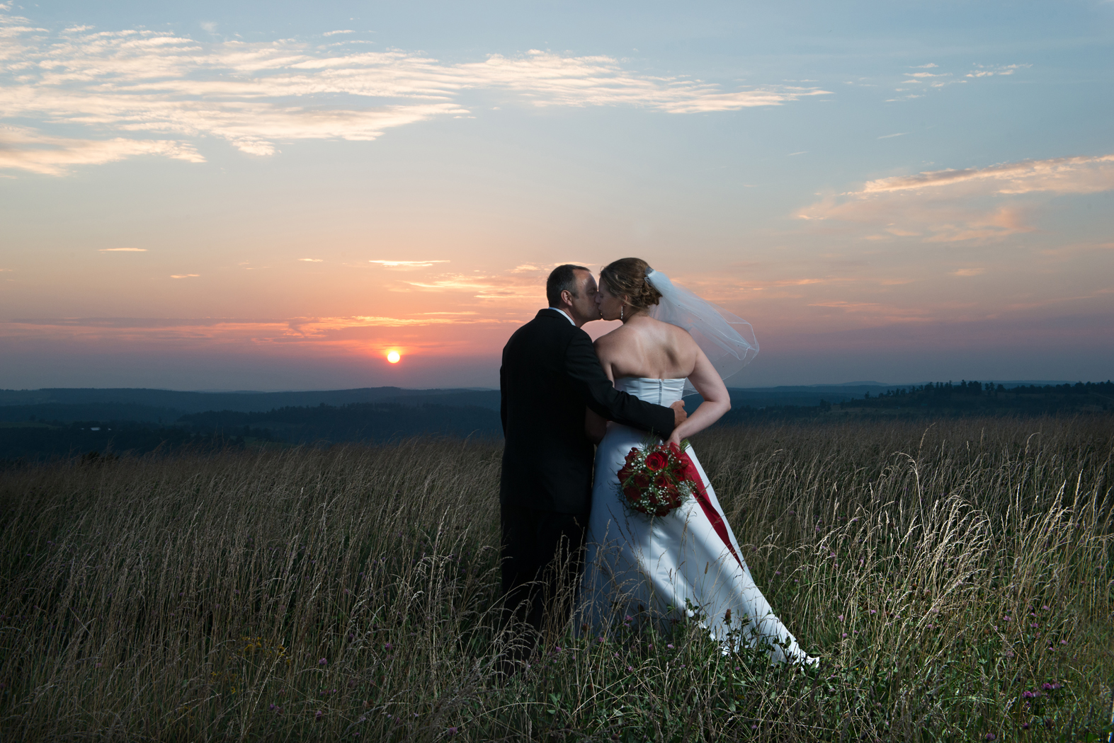 Bride and groom in meadow at sunset
