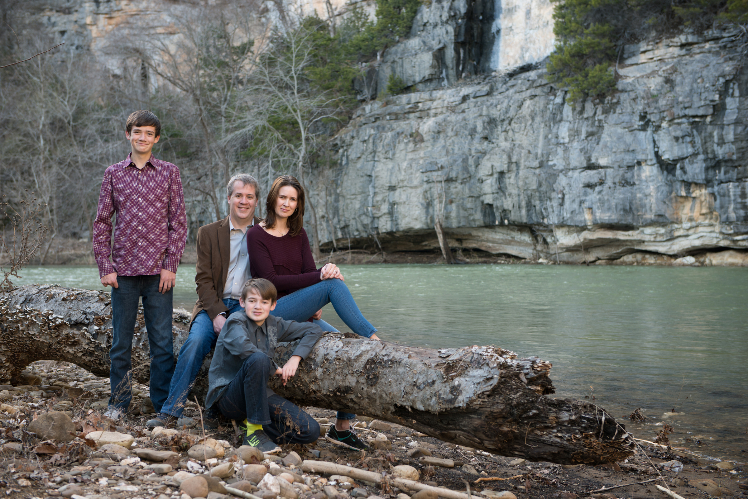 family of four sits on a log beside the Buffalo River