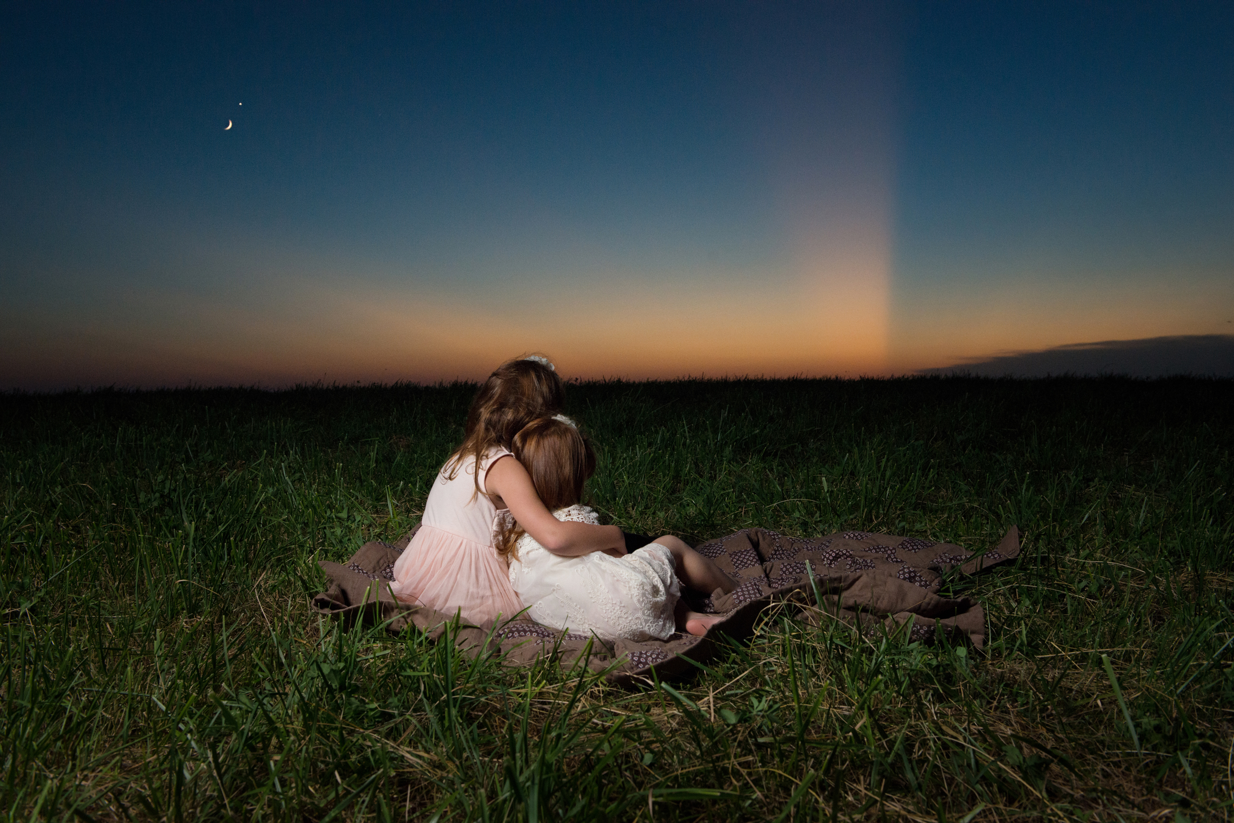Two little girls at sunset with crescent moon and star