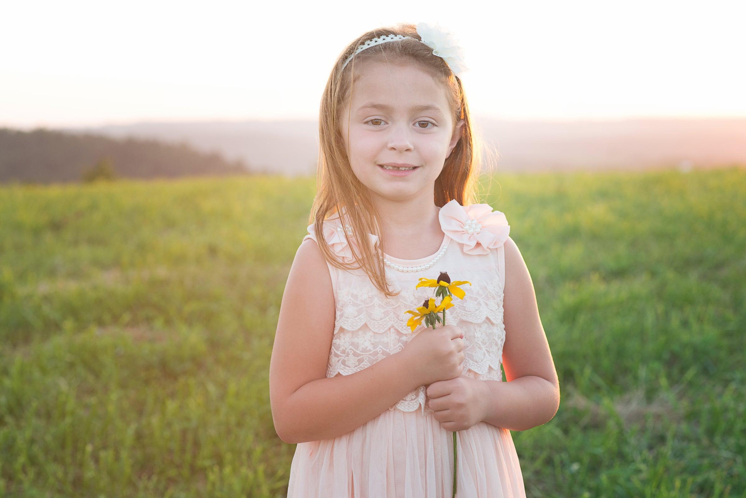 little girl holds a flower at sunset