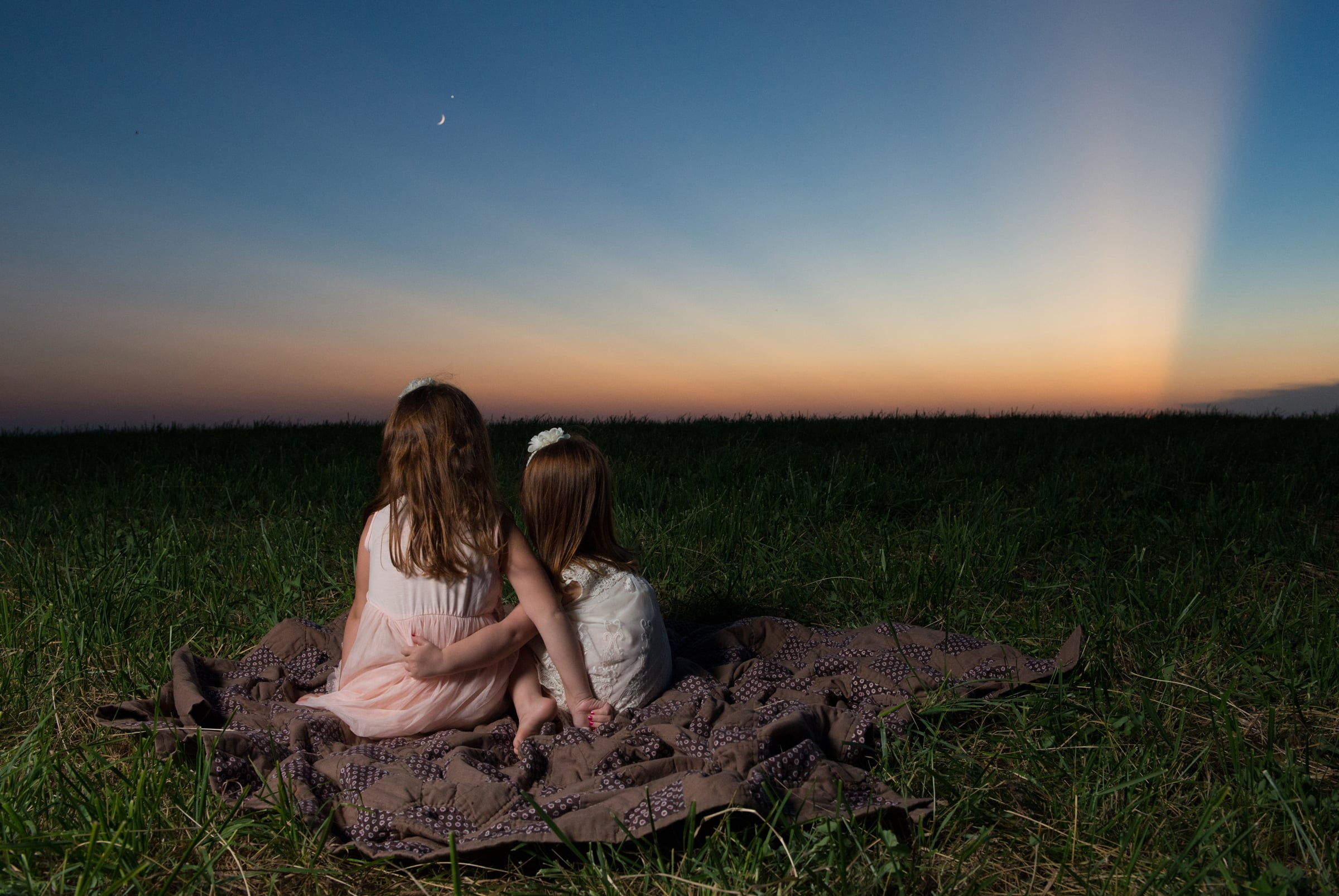 Two little girls watch a beautiful sunset on a mountain top