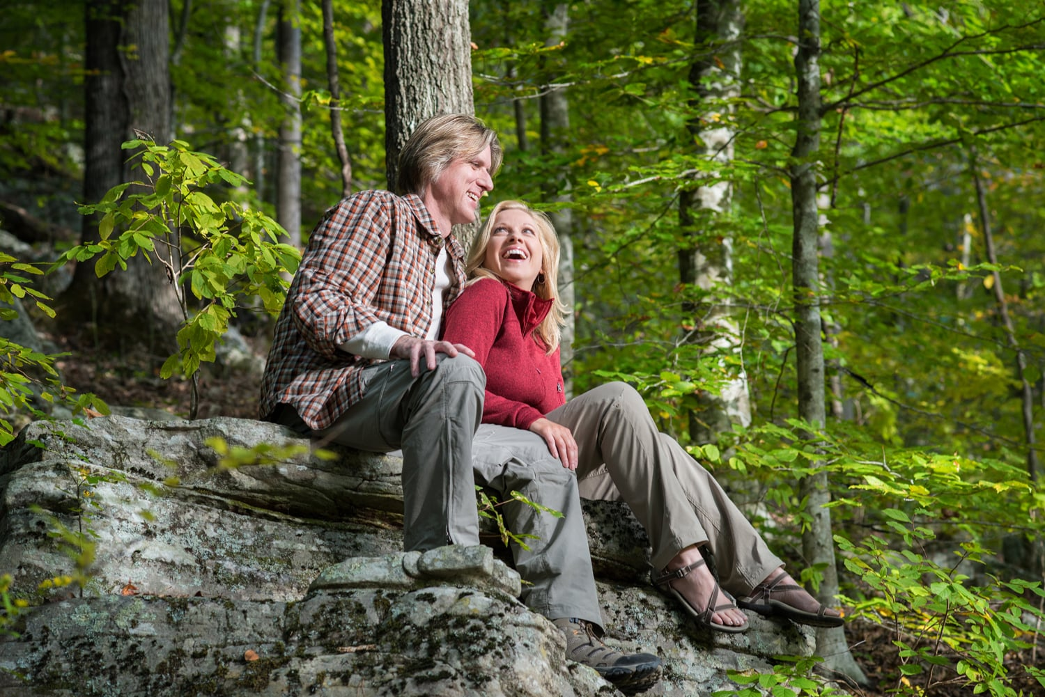 Couple laughing together sitting on a rock in the woods