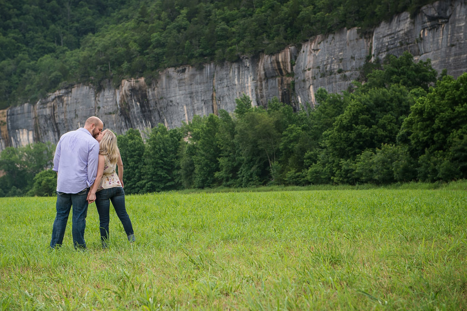 Couple kisses in a meadow by the Buffalo River
