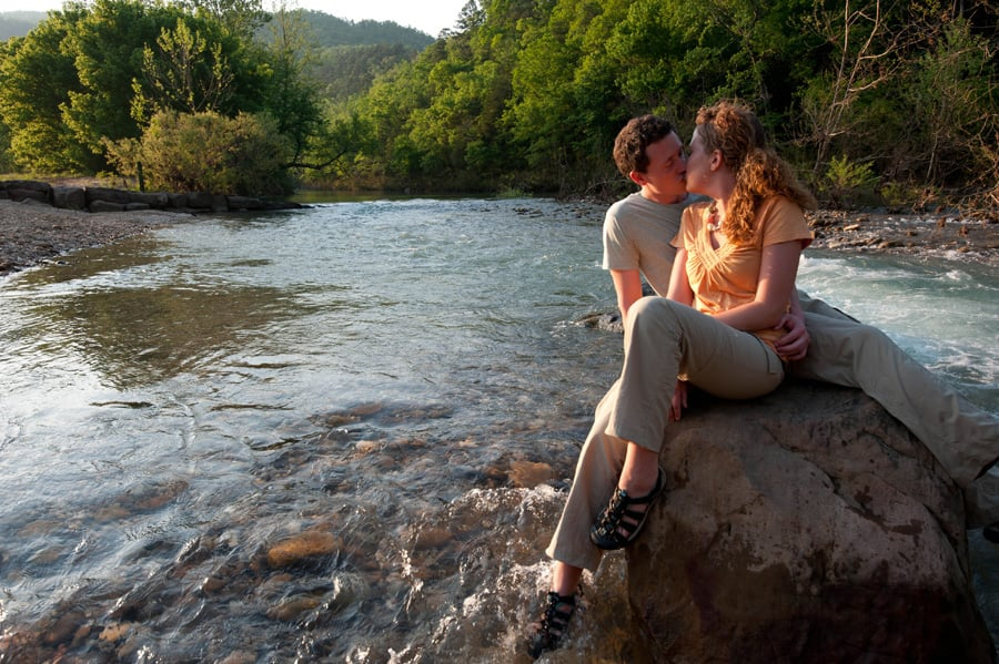 Couple kissing sitting on boulder in the Buffalo River
