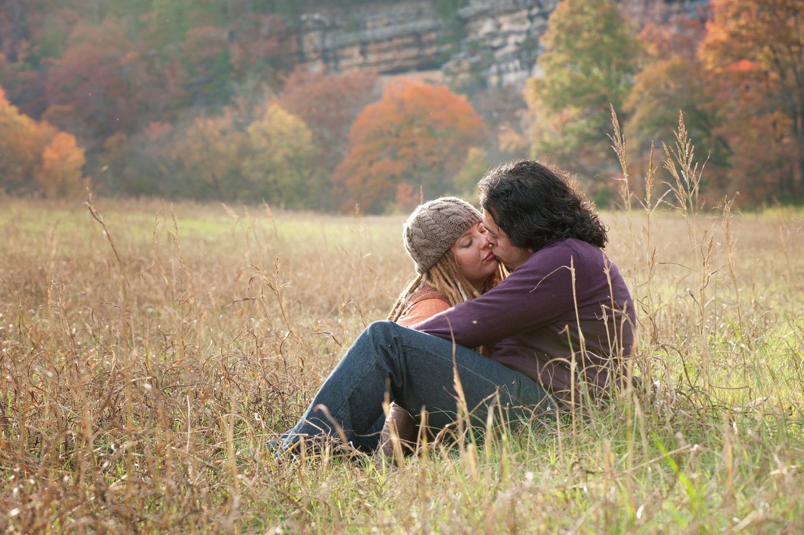 Couple kisses in a meadow in fall