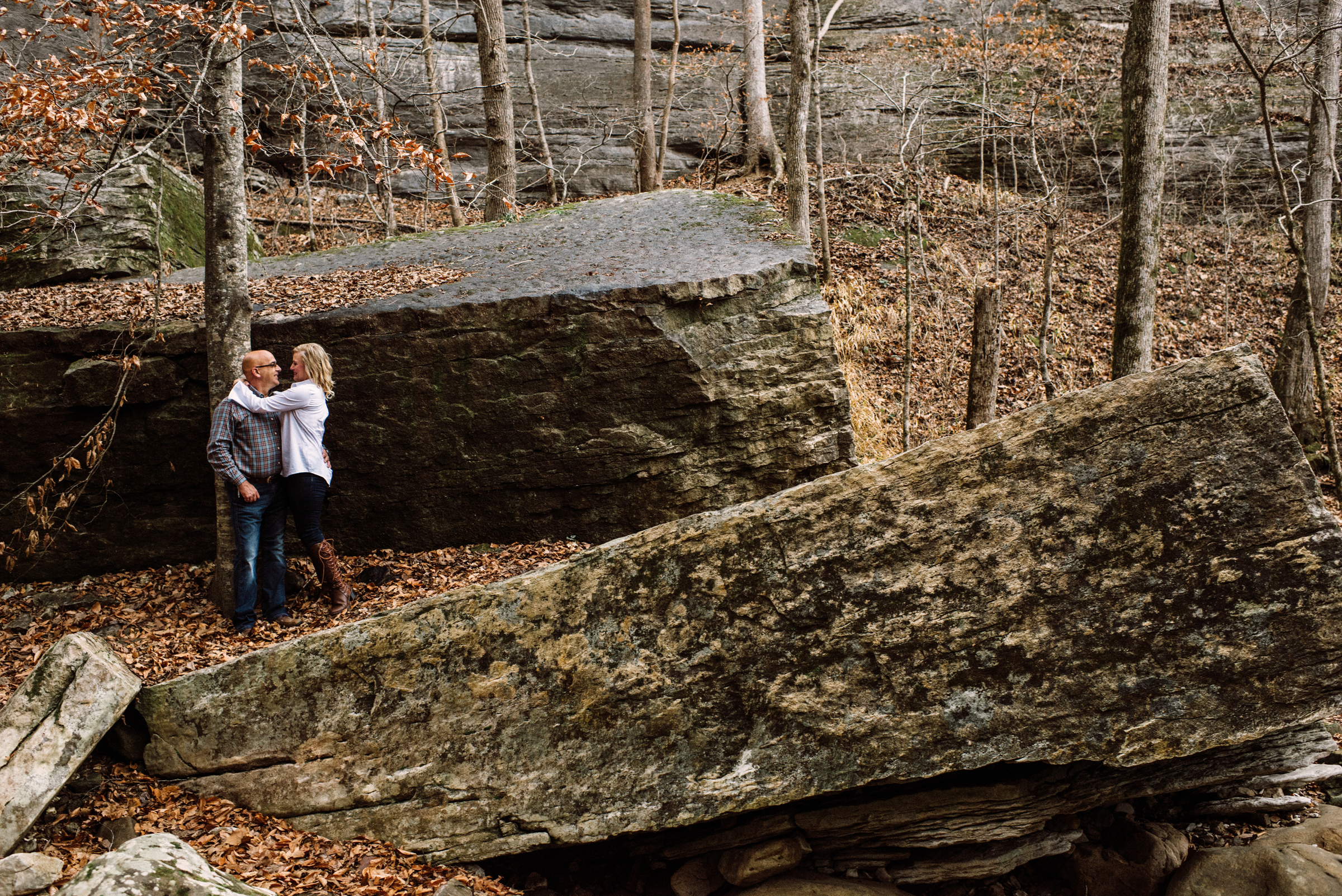 Couple among boulders in woods