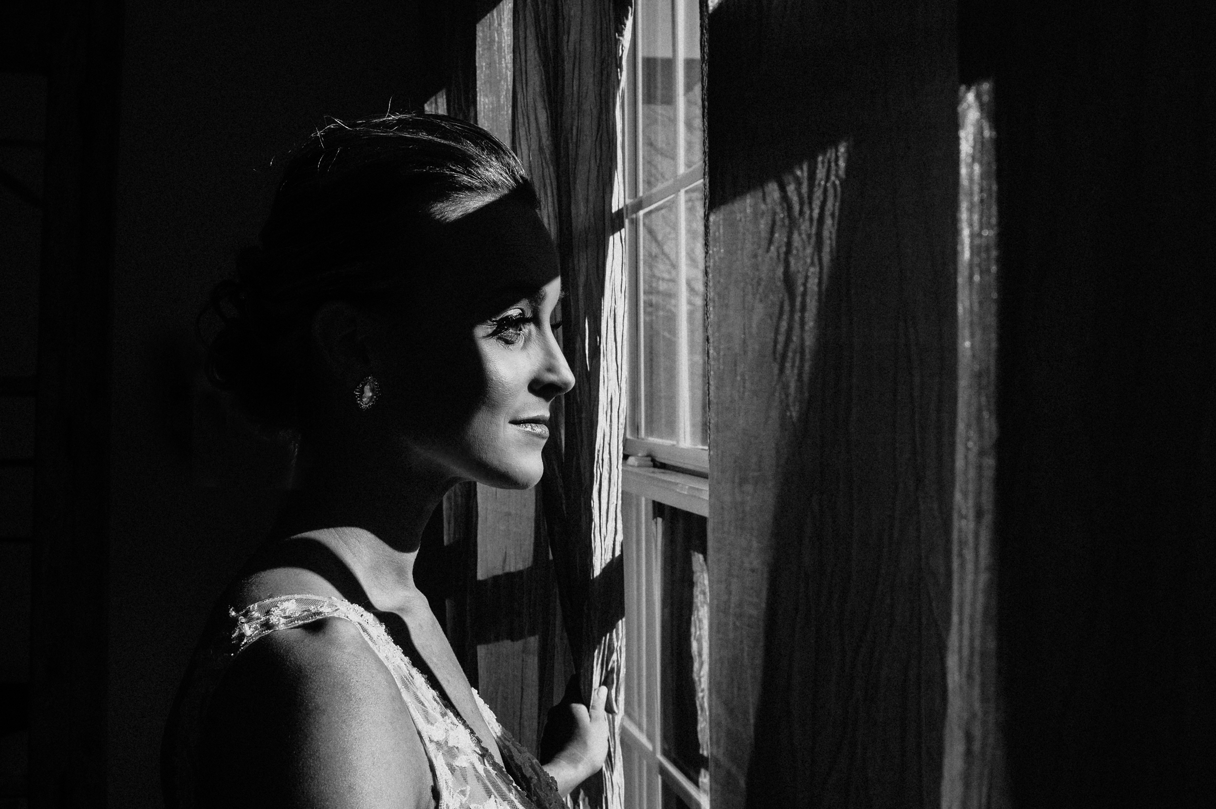 Artistic black and white image of bride looking out window