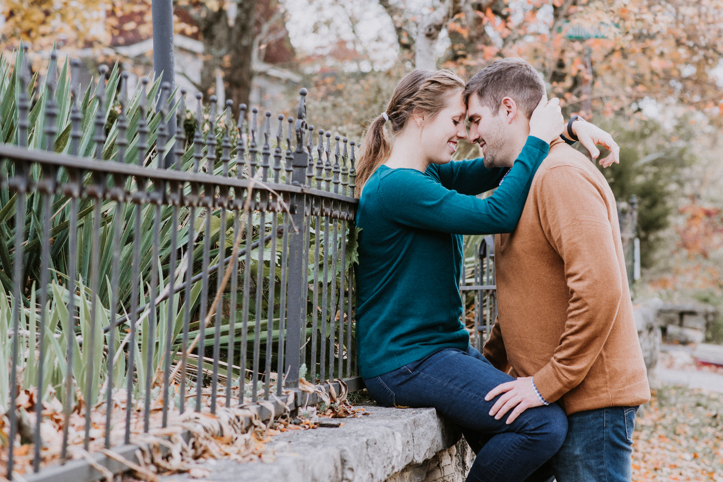 Engaged couple by wrought iron fence