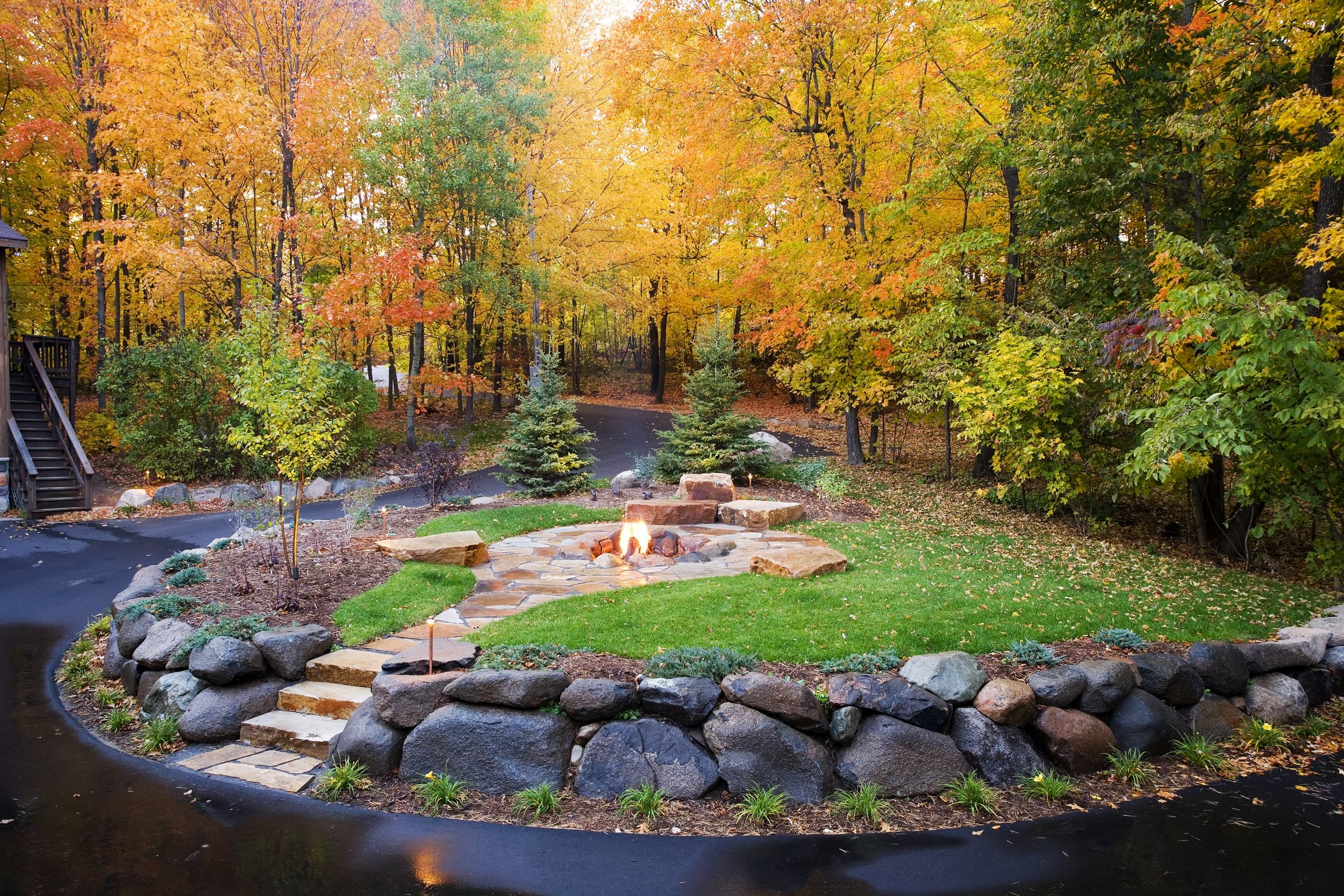 northwoods minnesota firepit with boulder walls and flagstone