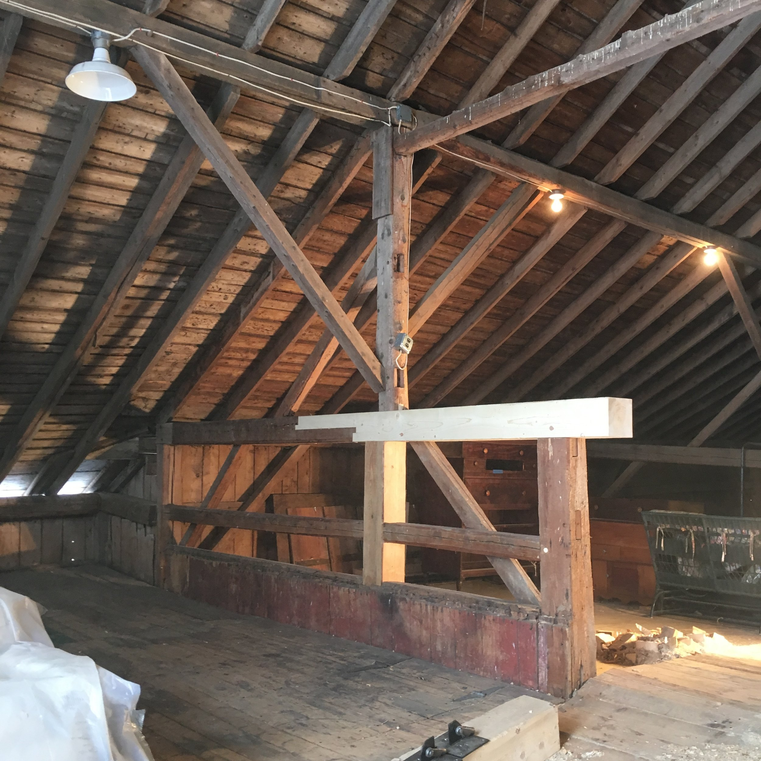 A typical repair to the barn haymow, with a scarfed end replacing a piece which had broken in its midsection. Purlin post is now adequately supported with an intermediate post, and running the replacement 1' into the aisle allowed for stronger joinery at the aisle post.