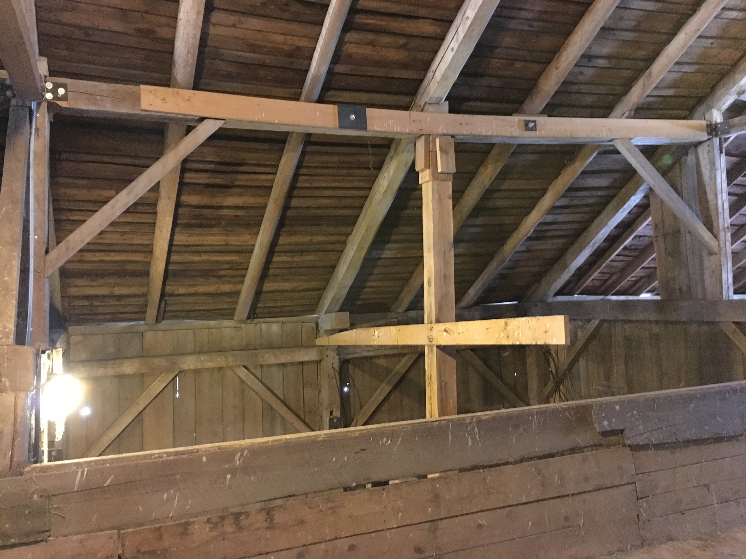 Another bent prior to repair, showing a post with no joinery into the principal rafter, and the wall tied to the post by a shattered remnant of modern dimensional 2x lumber,.