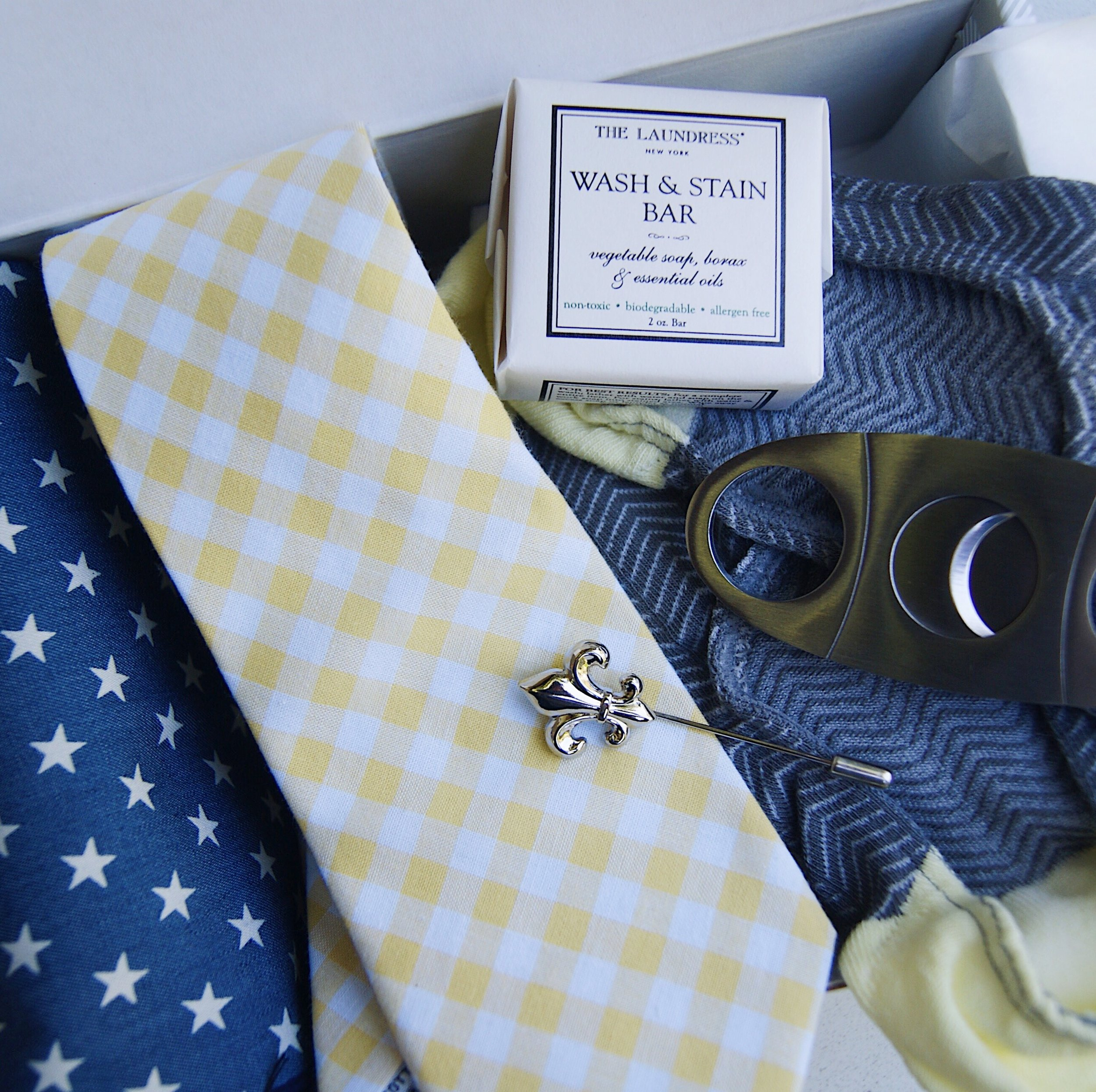 Some Sprezzabox goodies including a tie, pocket square, cigar cutter, pin, and socks.