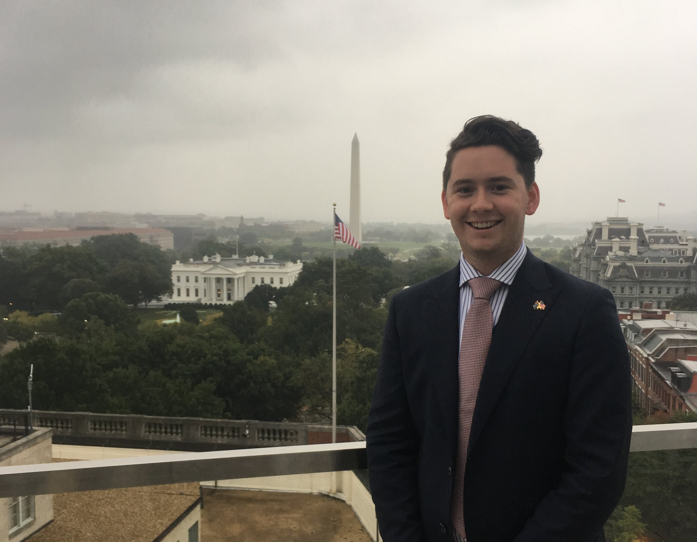 Arlen poses for a photo on the Baker-McKenzie rooftop overlooking the White House and the Washington Monument.