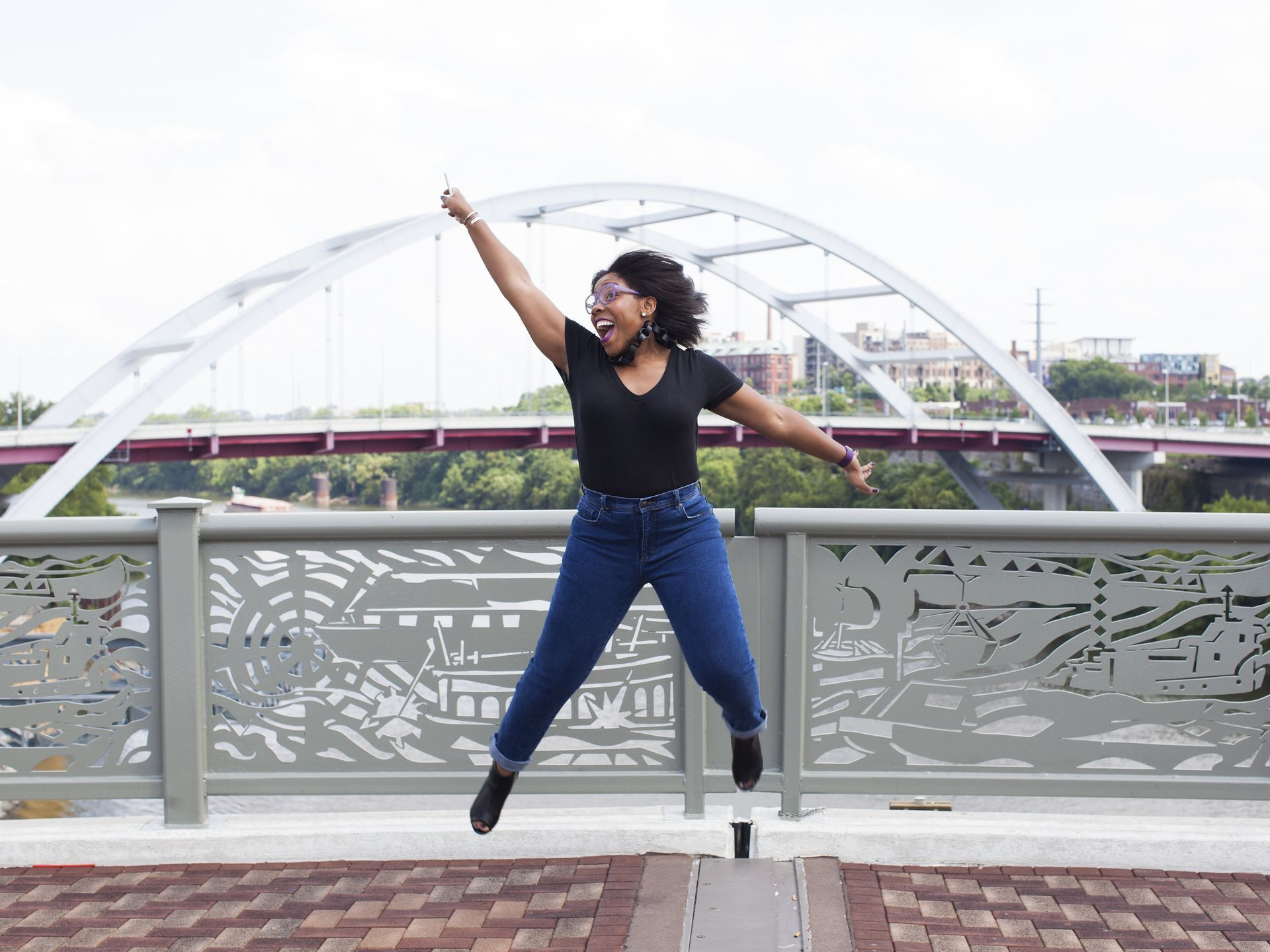 {Tennessean - Things to Do: Nashville's Favorite Selfie Spots} - Kia Jarmon reaches for the sky on this historic landmark that serves as a connector of Downtown Nashville and the East Nashville neighborhoods.