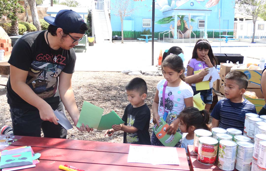 A volunteer with the FULL Project, a social entrepreneurial program headed by Pearl Park, a senior at Torrey Pines High School, helps during a recent distribution that provides food for elementary school students during school breaks. Courtesy photo