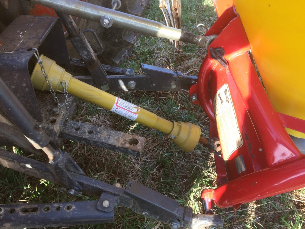 This is looking down at the back side of the tractor--the drawbar hitch is not in use (in the center), but the seeder is hooked up to the three points of the 3pt. The yellow shaft is the spinning PTO (more on that later).