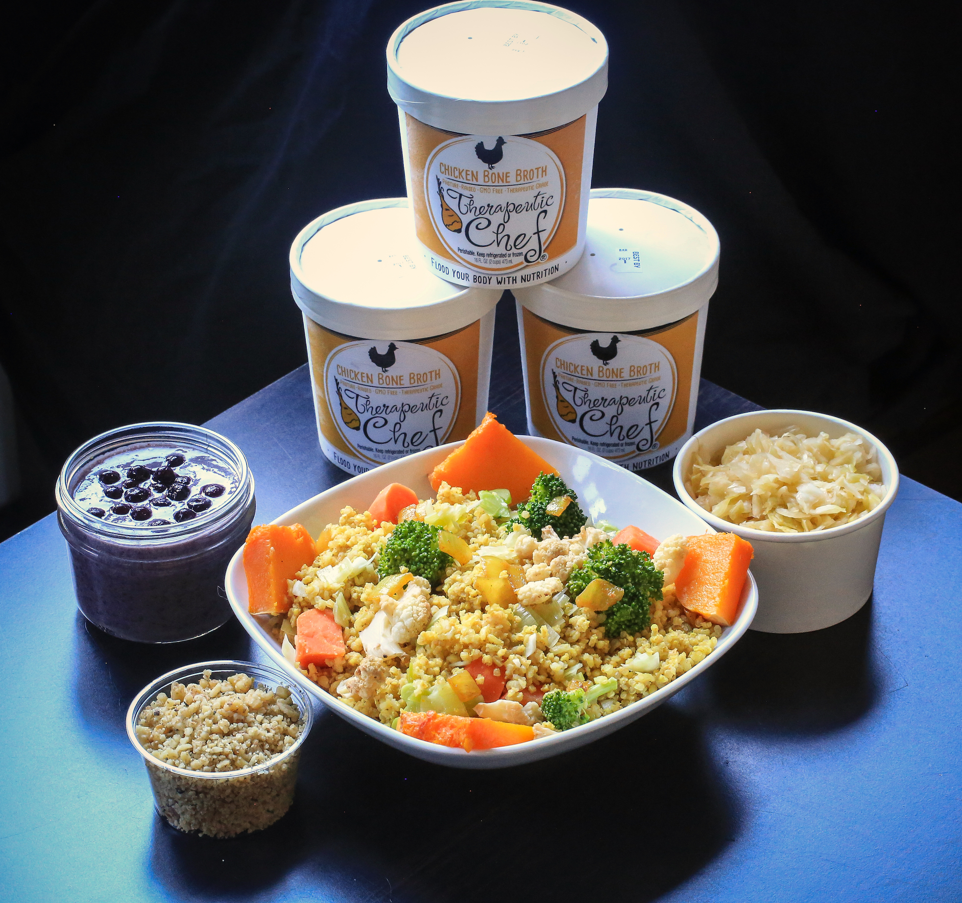 """Example of  some  of the items you will receive when you purchase your 3 day cleanse. From left to right: Blueberry Chia Pudding, Walnut-Hemp """"Cheese,"""" Quinoa Vegetable Salad, 3 containers of Chicken Bone Broth and probiotic-rich Sauerkraut."""