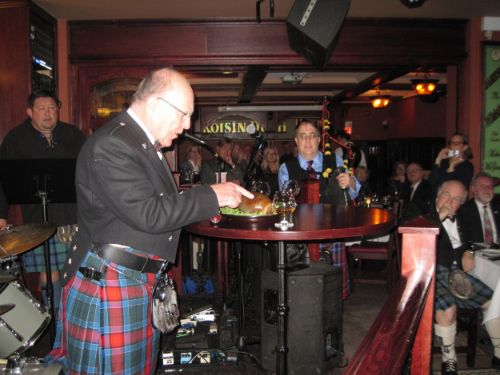 Stuart Jardine addresses the haggis, while event organizer Brian Lyall, piper ross may, and speaker john reid listen.