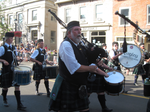 Before the race begins, a pipe band leads a procession of racers through the streets of Perth, Ontario.