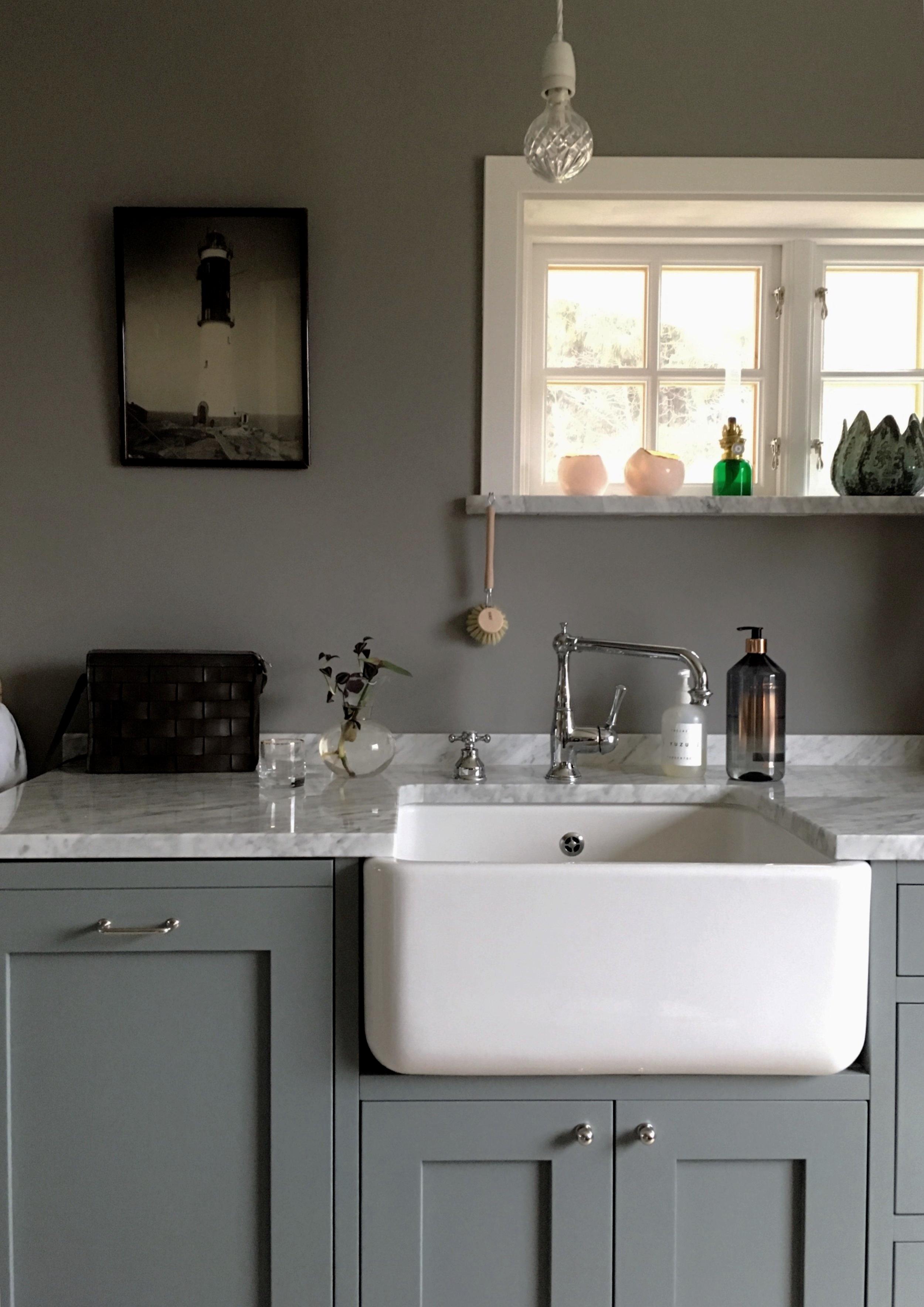 Sobert kök i grå toner med lite skärgårdsinslag på väggarna.