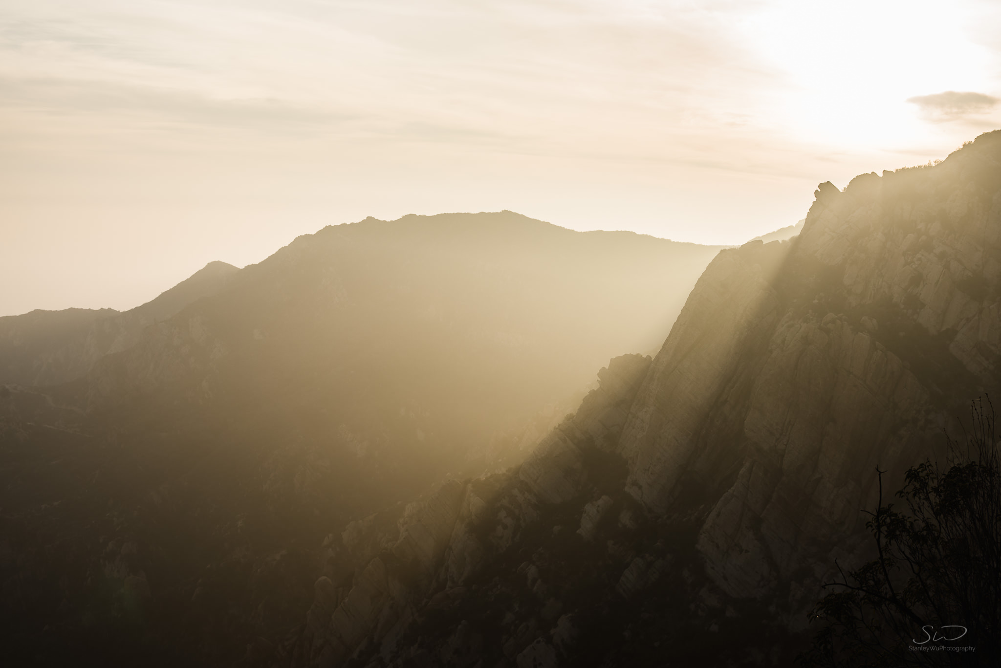 epic rays of sun coming over cliffs spilling into the valley in sunny malibu california