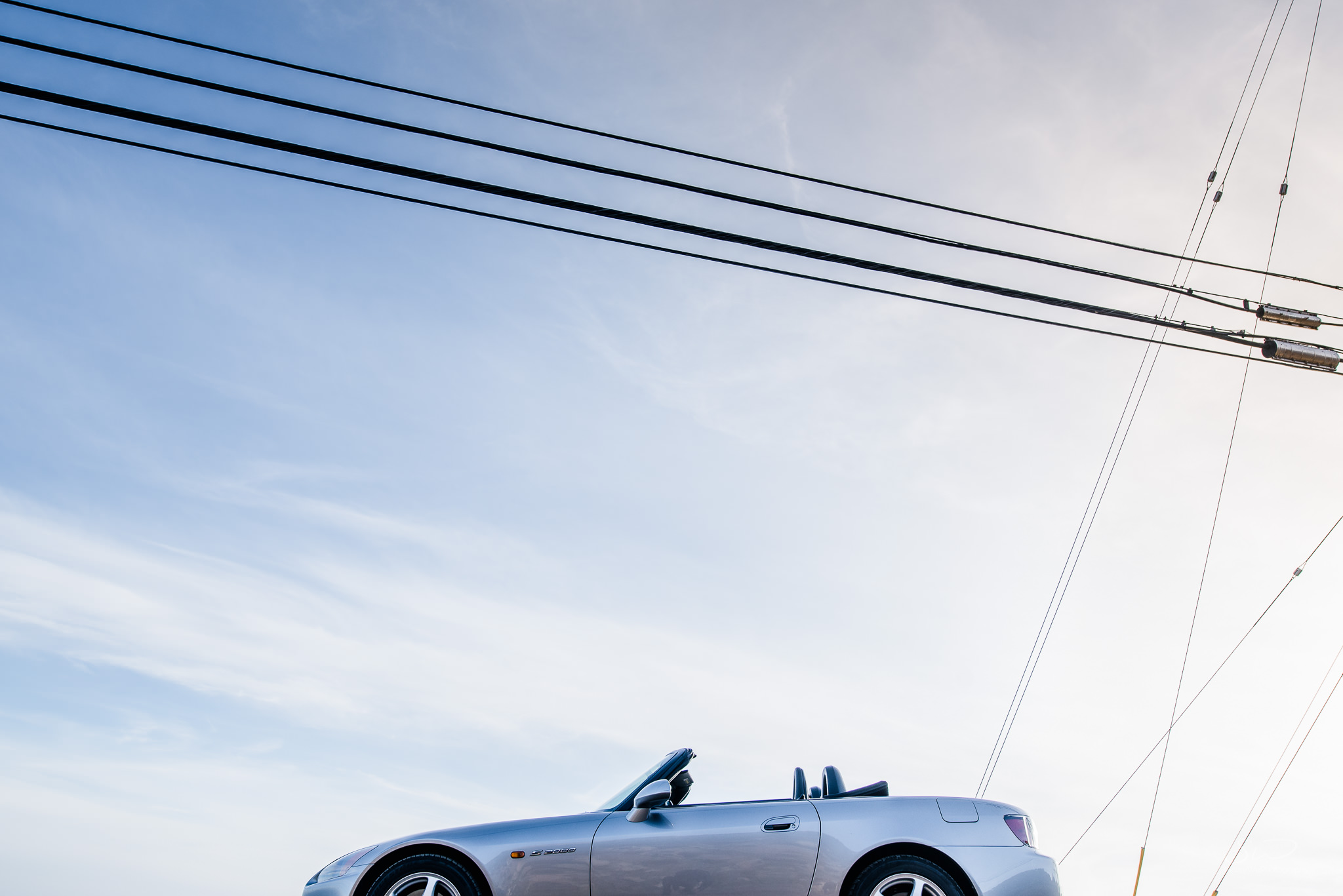 epic minimalism photo of blue skies and silver honda s2000 in malibu sunny california