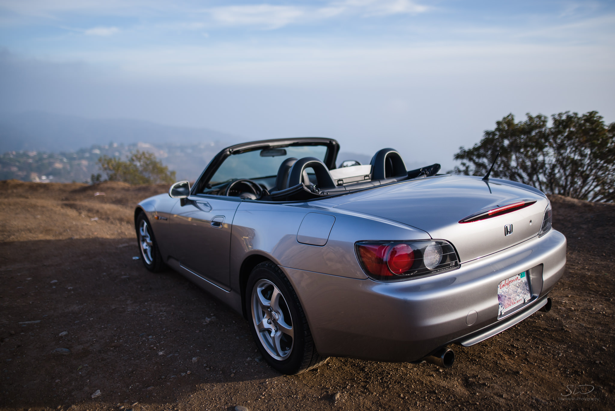 rear view of honda s2000 facing the edge of a cliff overlooking sunny blue skies in malibu california