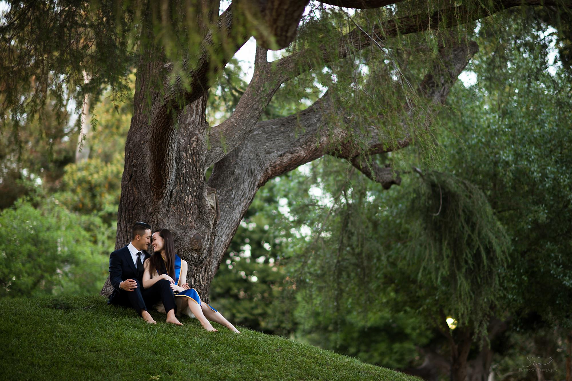 los angeles graduation senior portrait couple having a beautiful moment under a tree in a forest background at ucla