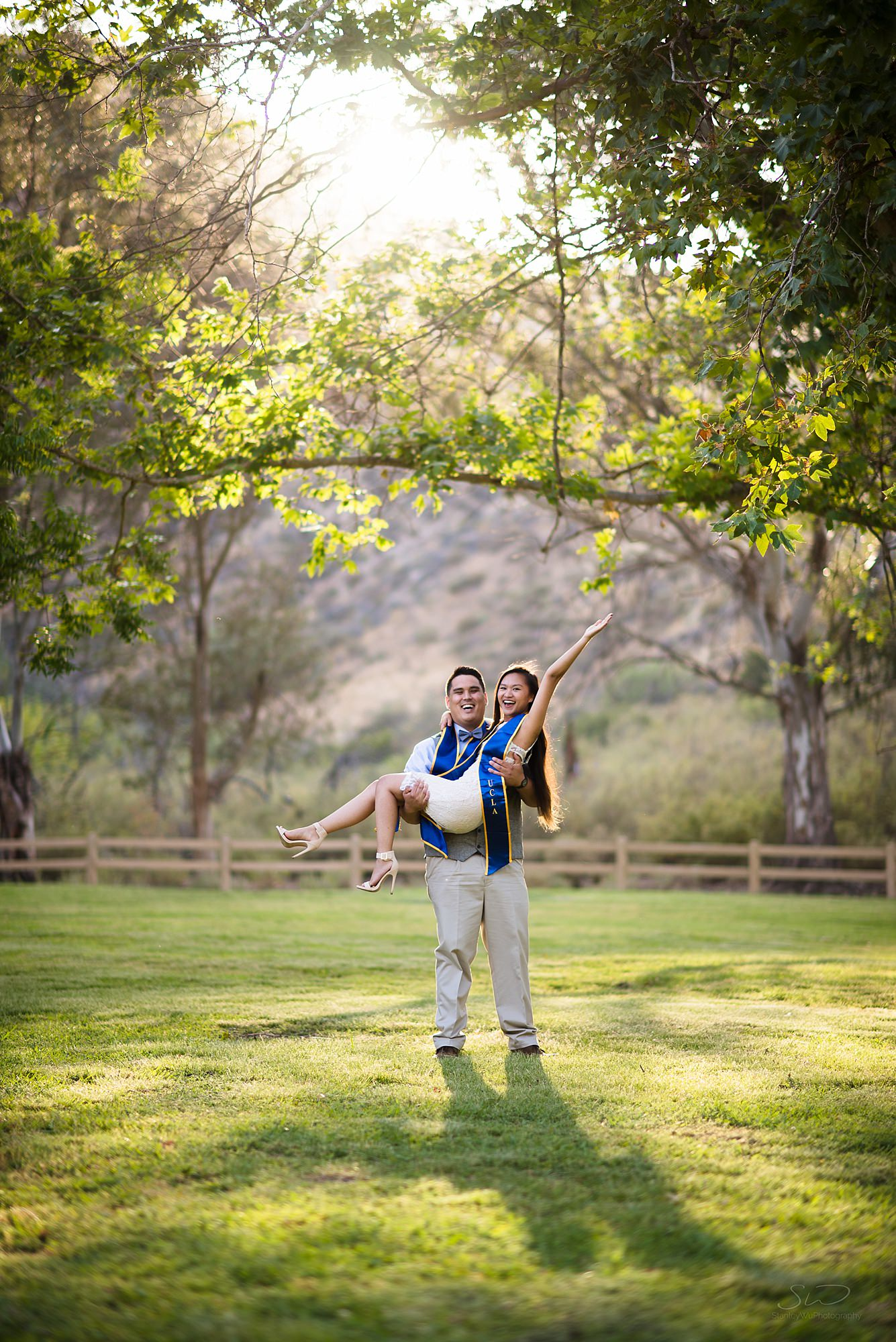 beautiful graduation senior portrait of a couple and the boyfriend carrying the girlfriend in a grassy area at omelveney park in san fernando valley in southern california