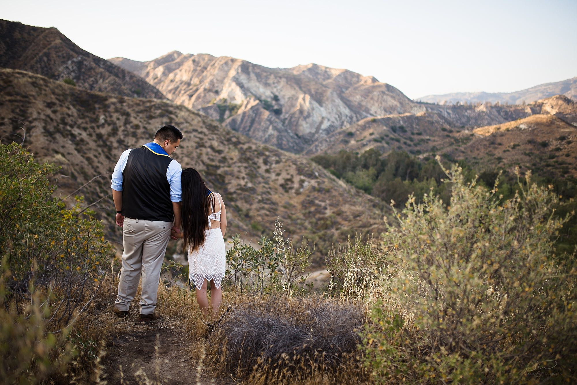 epic graduation senior portrait of a couple standing on a cliff before mountains in the background at san fernando valley in los angeles