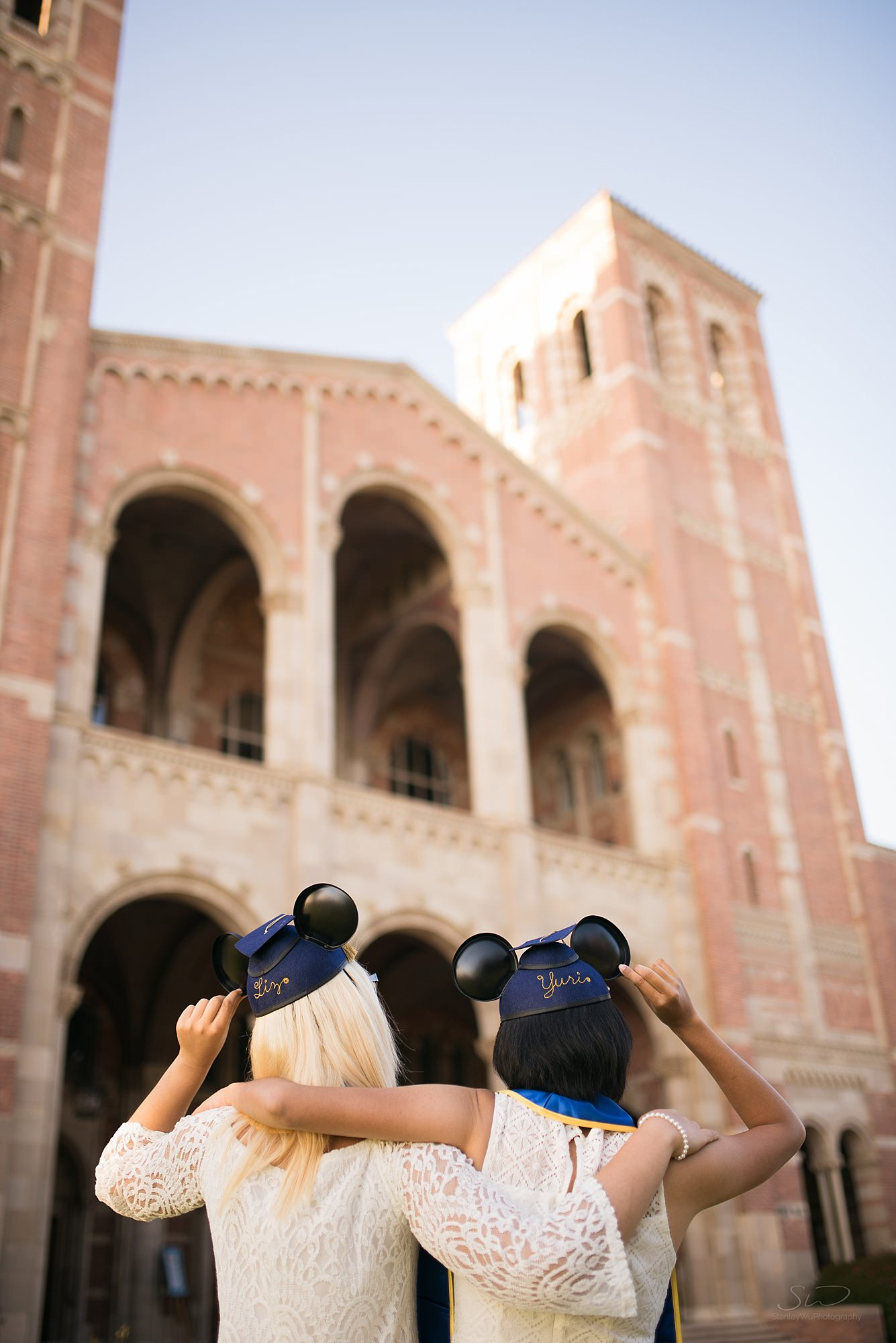 fun graduation senior portrait of two girls back facing the camera with disney hats at ucla in los angeles