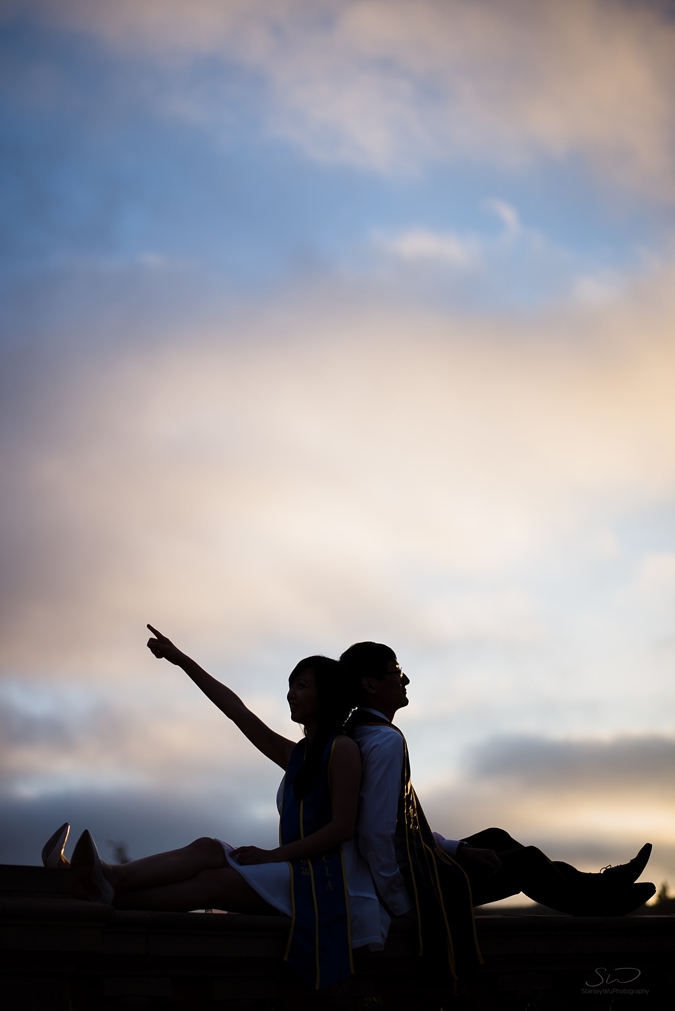graduation senior portrait silhouette of a couple with backs facing each other in front of a blue sky with the girl pointing off into the distance at ucla in los angeles