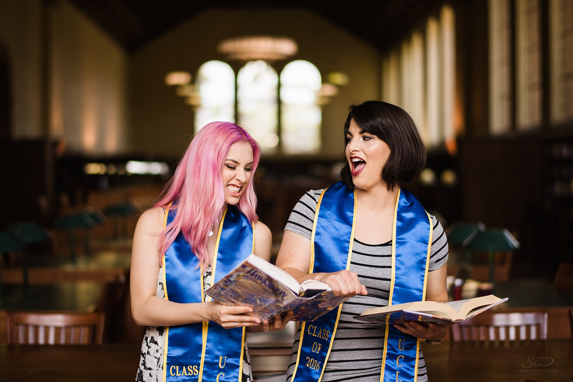 cute graduation senior portrait of two white girls with books having fun in the library at ucla in los angeles